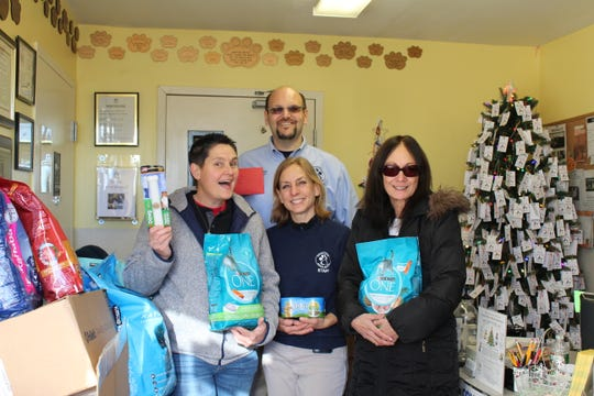On Tuesday, Dec.18, SCLSNJ donated more than1000 pounds of dog and cat food, litter, office supplies, and more to the Somerset Regional Animal Shelter (SRAS). Pictured are Sherri Lynn, former library commissioner; Brian Bradshaw, shelter manager; Nancy Gedbaw, kennel manager and animal control officer; and Edith Lit, SCLSNJ operations supervisor, posing with some of the donations Library staff and patrons made to the Somerset Regional Animal Shelter.