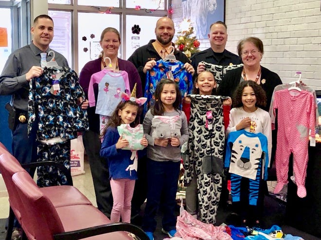 The Linden Police Department's two unions donated 25 pairs of pajamas to Linden School No. 10's drive. Pictured from left are Detective Tim Hubert, president of Linden PBA Local 42; School No. 10 paraprofessional Kristin Zuk; Principal David Walker; Sgt. Joseph Birch, president of the Linden Police Superior Officers Association; and teacher Fran Czylek, who organized the drive. The children are Brielle Suros, Gianna Cedeno, Natalie Diaz and Jeremiah Fortuna.