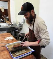 Andy Lane of Hand Hewn Farm sharpens a knife prior to the start of a recent hog workshop in which participants were taught how to take a pig from pasture to plate. Upcoming workshops include how to make salami and cure meats.