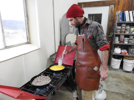 Doug Wharton of Hand Hewn Farm prepares breakfast of eggs from chickens and sausage from pigs raised on the farm in Fresno. The farm uses natural methods and holds workshops on how to humanely kill and butcher animals.