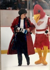 Mary Schroeder, Detroit Free Press sports photographer, is helped across the ice by the Detroit Wings mascot to her shooting position at Joe Louis Arena in Detroit.