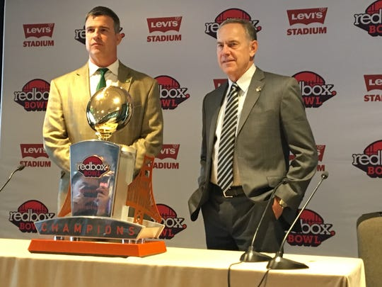 Oregon coach Mario Cristobal, left, and Michigan State coach Mark Dantonio pose with the Redbox Bowl trophy during a press conference Friday, Dec. 28, 2018 at the Hyatt Regency Hotel in San Francisco.