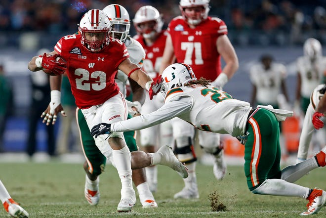 Wisconsin running back Jonathan Taylor (23) breaks a tackle attempt by Miami defensive back Sheldrick Redwine during the first half of the Pinstripe Bowl on Thursday.