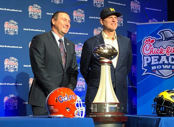 Florida coach Dan Mullen and Michigan coach Jim Harbaugh pose for photos at the Peach Bowl news conference on Friday.