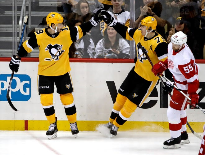 Pittsburgh Penguins' Derick Brassard (19) celebrates his empty-net goal with Evgeni Malkin (71) as Detroit Red Wings' Niklas Kronwall (55) skates back to the bench during the third period on Thursday.
