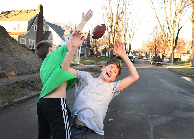 James O'Connor, 13, breaks up a pass intended for Quinn O'Connor, right, 15, thrown by their father John O'Connor (not pictured) in the middle of Lawson street in Royal Oak on an unseasonably warm and sunny Friday afternoon, December 28, 2018.