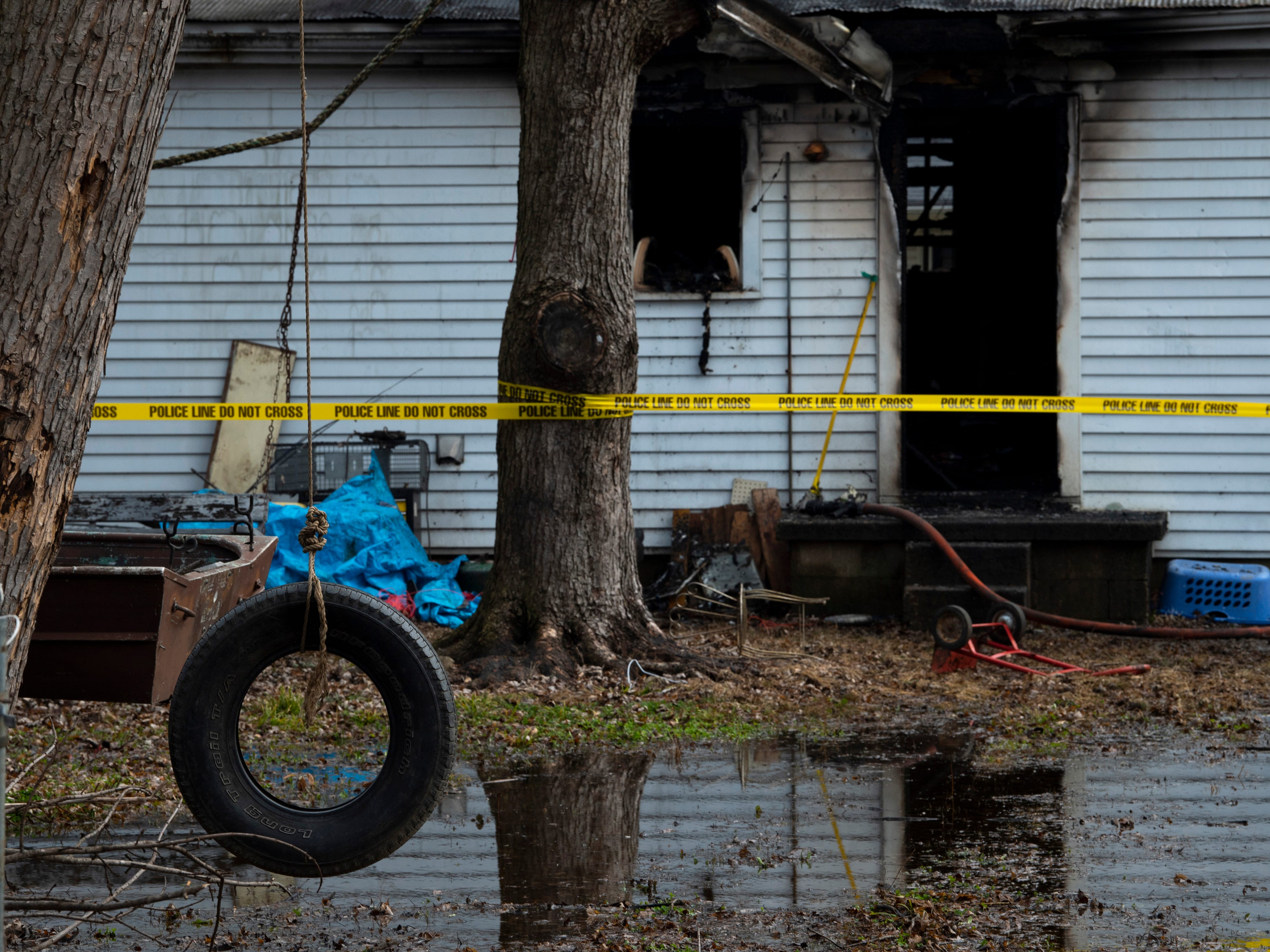 Water pools in the backyard of a home at 1027 15th Street in Tell City, Ind., Friday morning. An early morning fire took the lives of three children in the home. Their mother and two other siblings escaped the blaze with non life-threatening injuries.