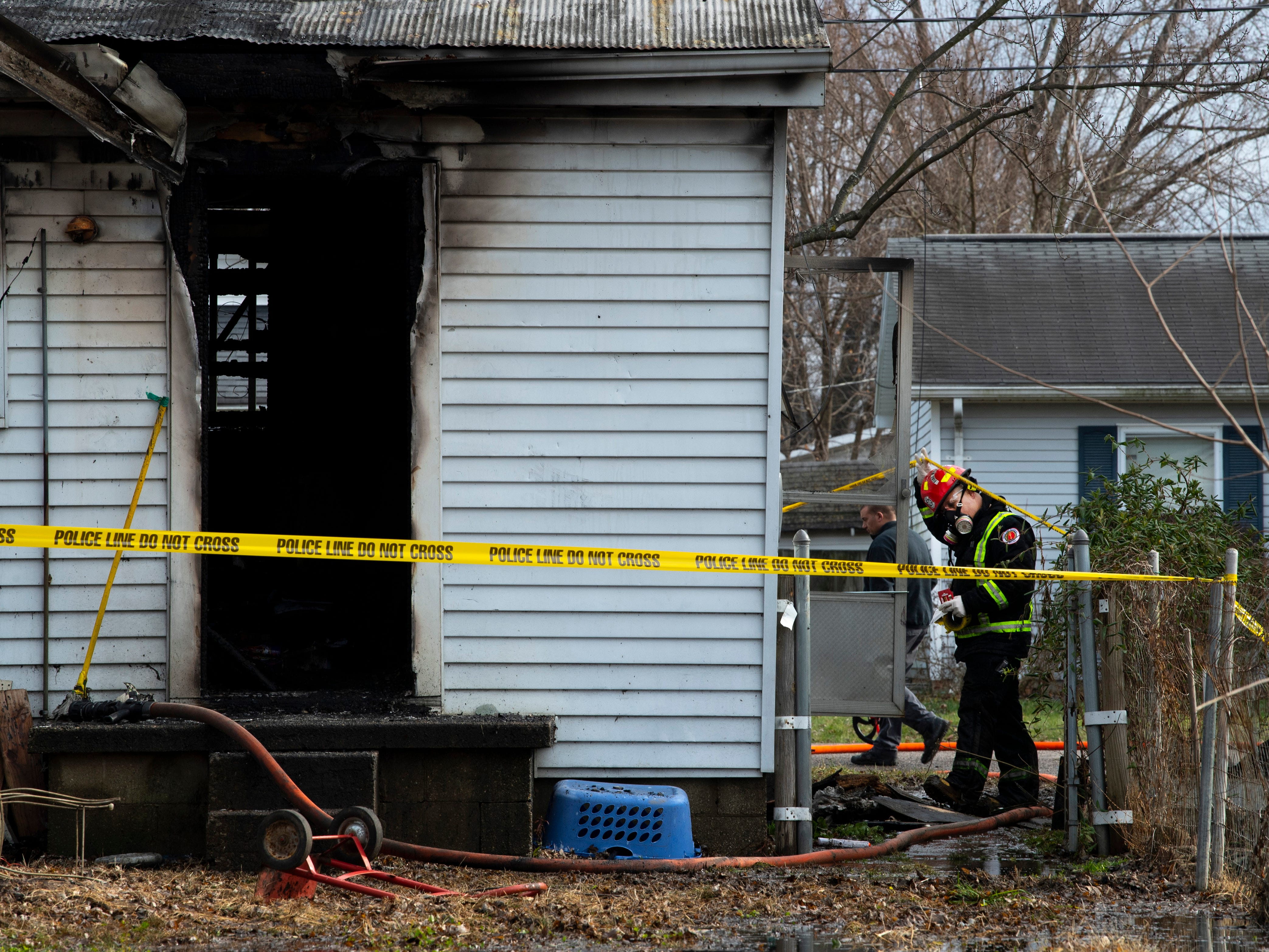 A fire investigator enters a home at 1027 15th Street in Tell City, Ind., Friday morning. A fire in the home early Friday morning killed three siblings – all under the age of 12 – and the mother and two other children escaped the blaze with non life-threatening injuries.