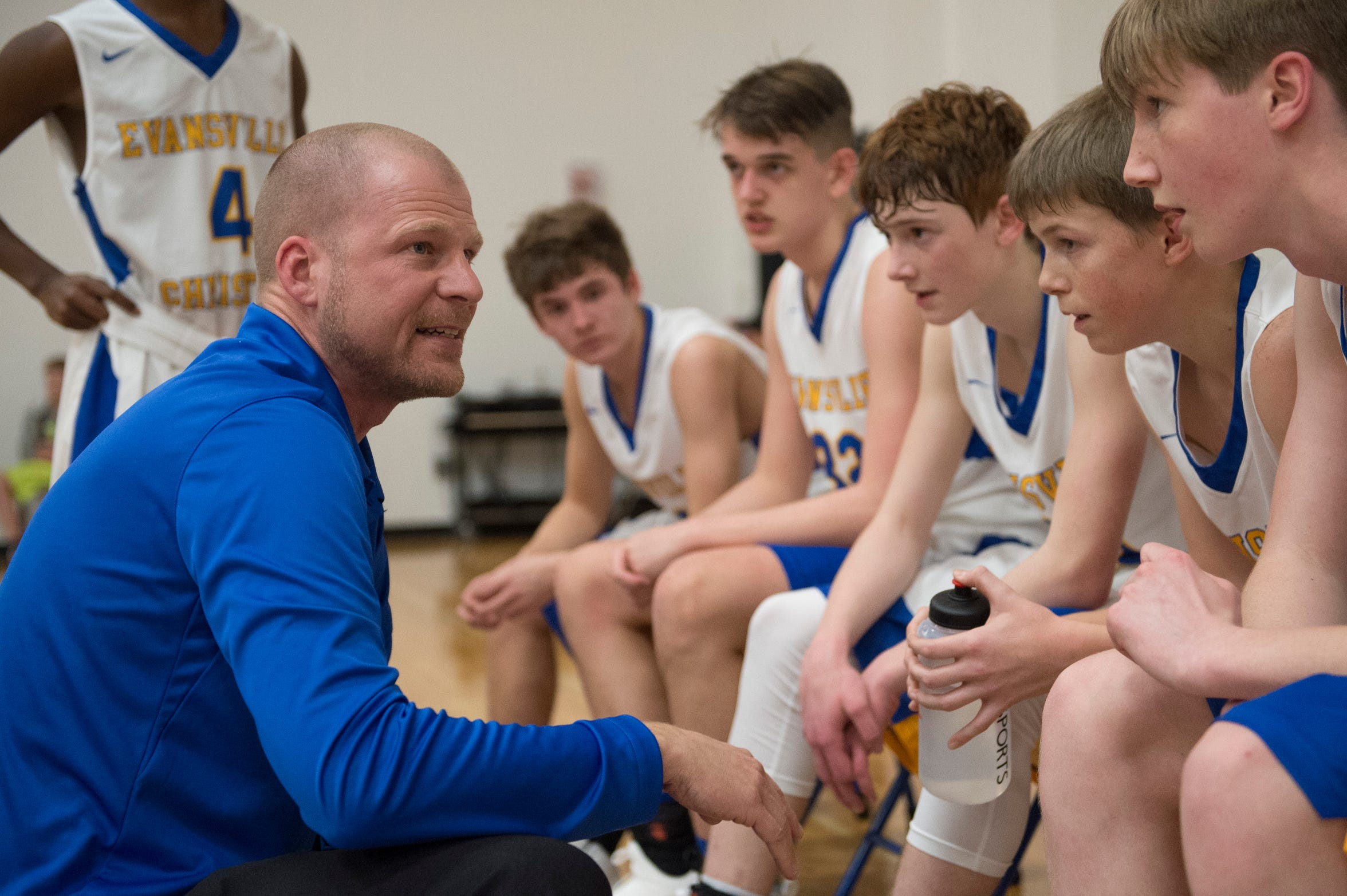 Evansville Christian's Head Coach Aaron Thompson excites his team during a timeout in the schools first-ever home game against the Cannelton Bulldogs Friday, Dec. 14, 2018.