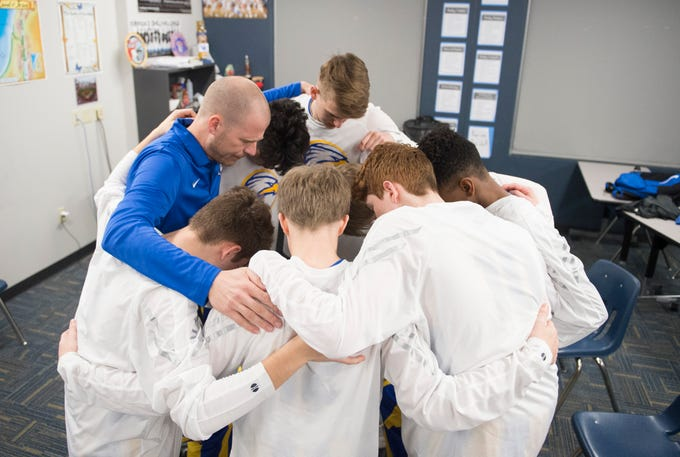The Evansville Christian School boys' basketball team pray before their first-ever home game against the Cannelton Bulldogs Friday, Dec. 14, 2018.