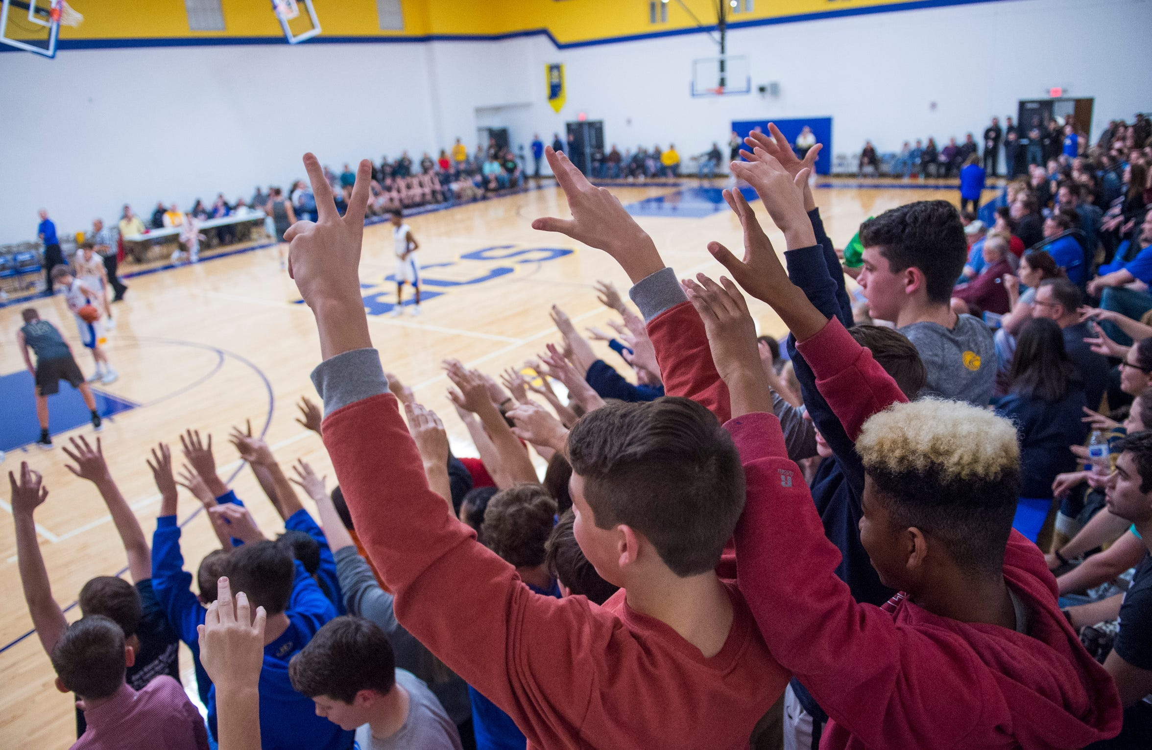 Evansville Christian School fans hold up their hands while Connor Sharp (12) shots one from the line during the schools first-ever home game against the Cannelton Bulldogs Friday, Dec. 14, 2018.