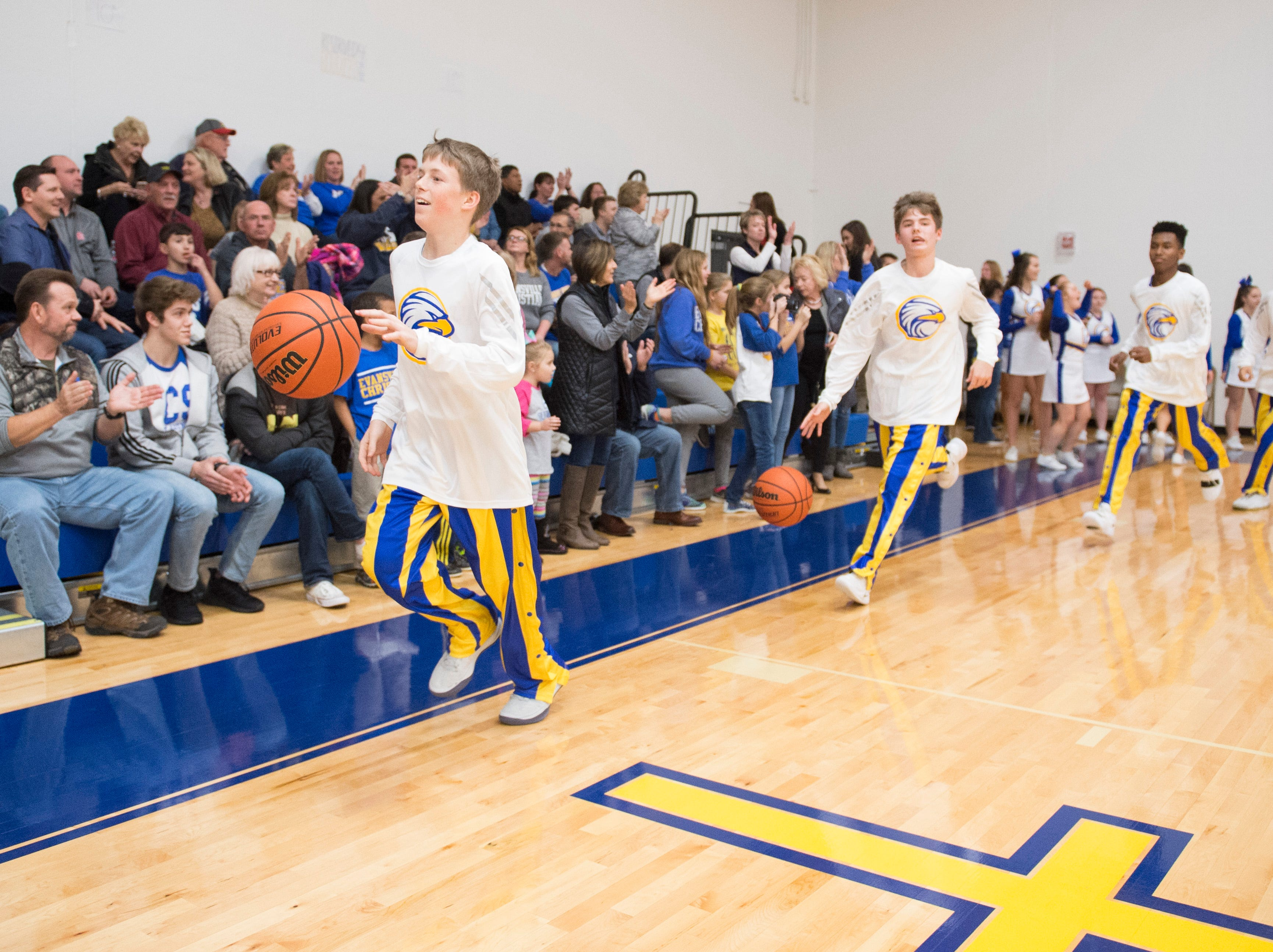 Evansville Christian's Connor Sharp (12) leads the boys' basketball team around the court for the fans before their first-ever home game Friday, Dec. 14, 2018.