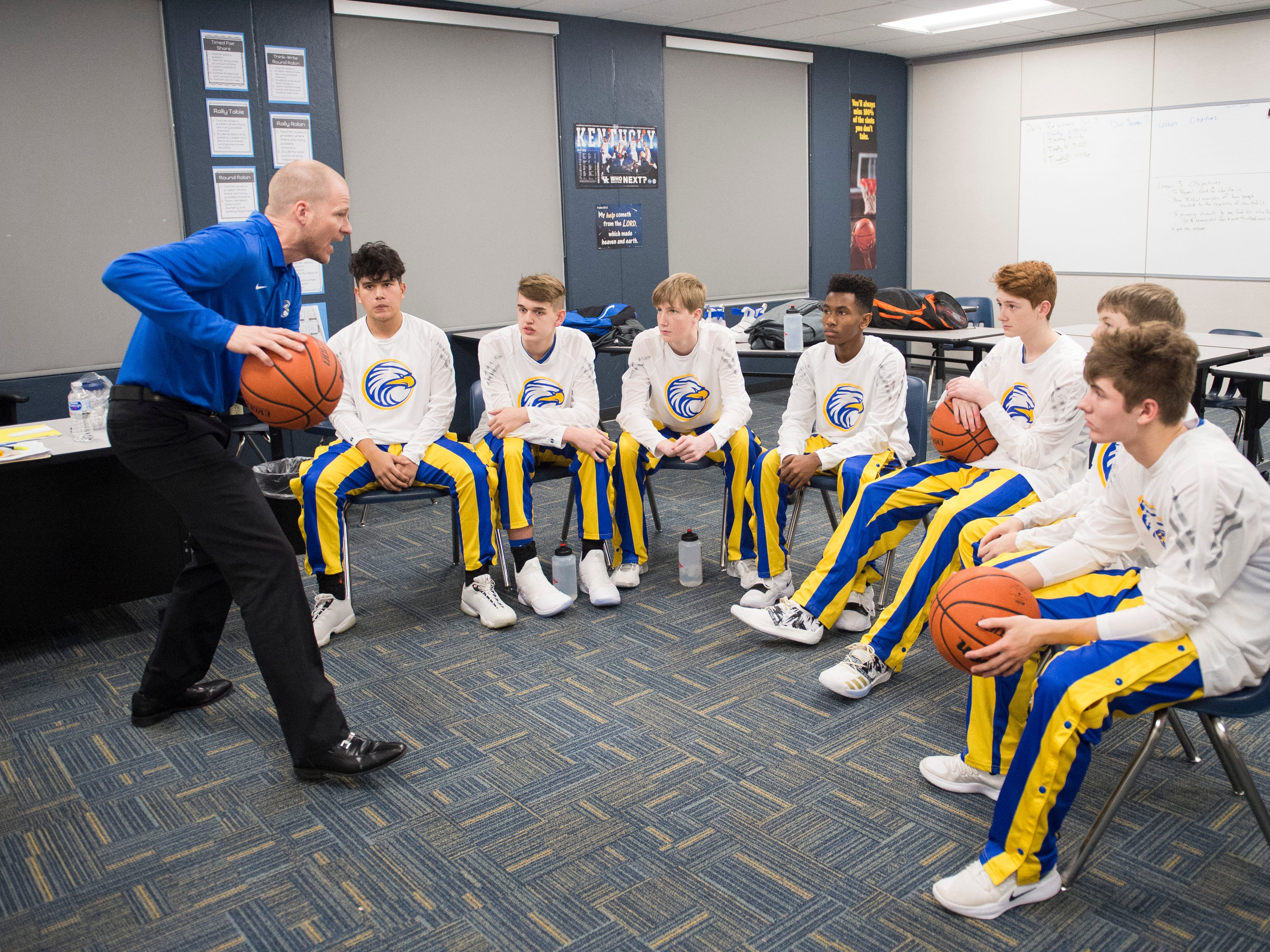 Evansville Christian's Head Coach Aaron Thompson  goes over a game plan before the Evansville Christian School Eagles take on the Cannelton Bulldogs in the schools first-ever home varsity boys basketball game Friday, Dec. 14, 2018.
