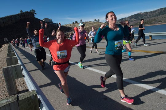 Runners celebrate reaching one mile in the course as they cross Dixon Canyon Dam along Horsetooth Reservoir during the Horsetooth Half Marathon on Saturday, April 14, 2018.