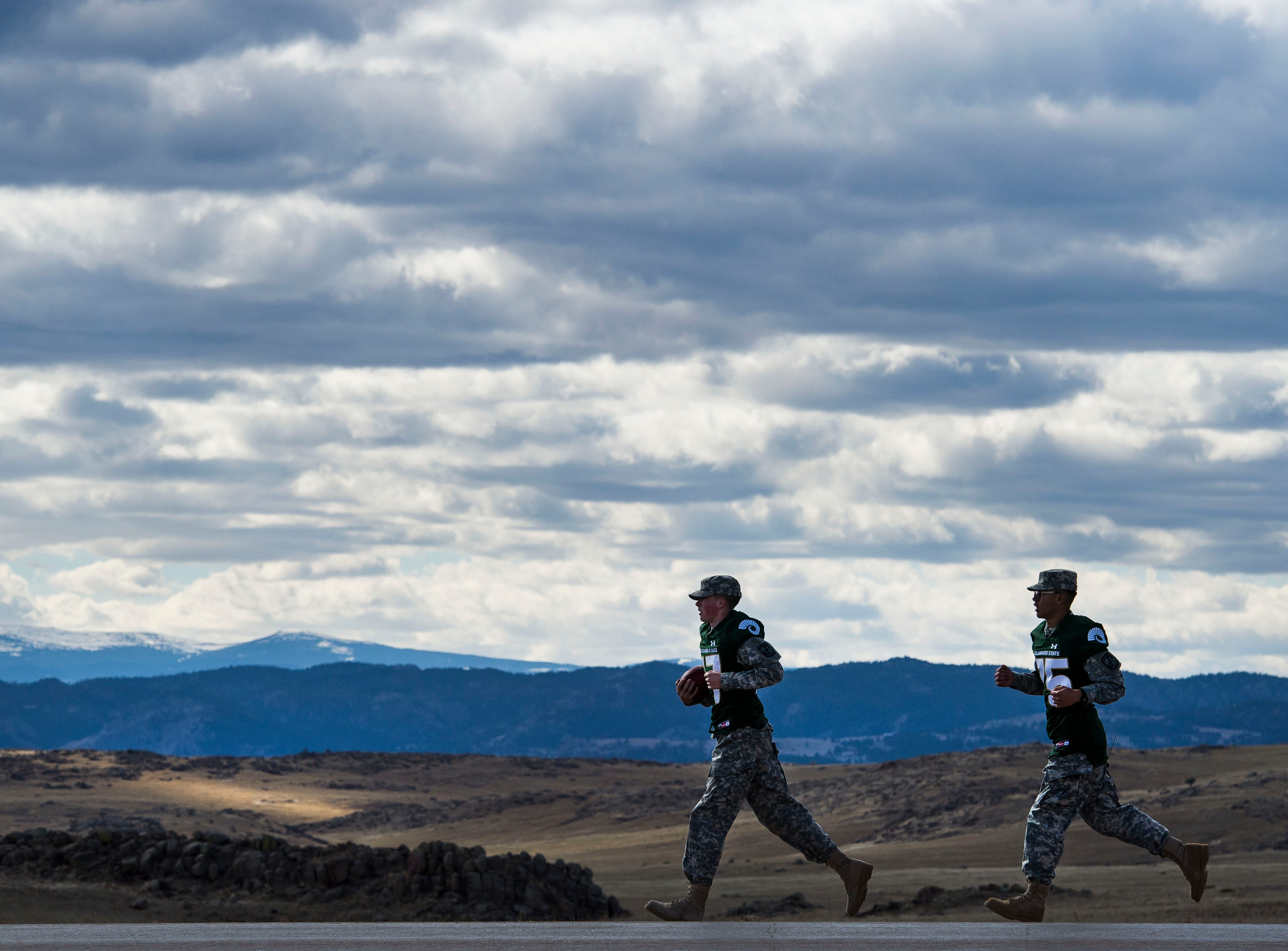 "Colorado State University Army ROTC cadets run the ""Border War"" game ball South on highway 287 on their way back from the state border between Colorado and Wyoming on Thursday, Oct. 25, 2018, in Larimer County, Colo."