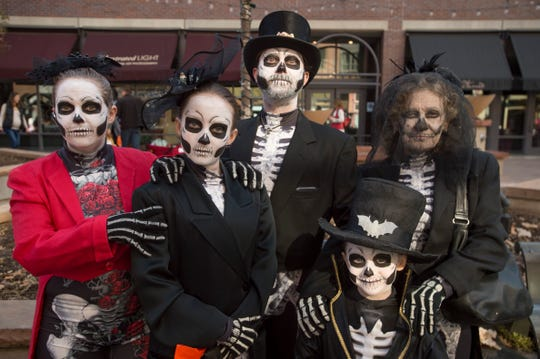 A family of skeletons poses for a photo during Tiny Tot Halloween on Wednesday, October 31, 2018. Downtown businesses offer the family friendly Halloween fun each year.