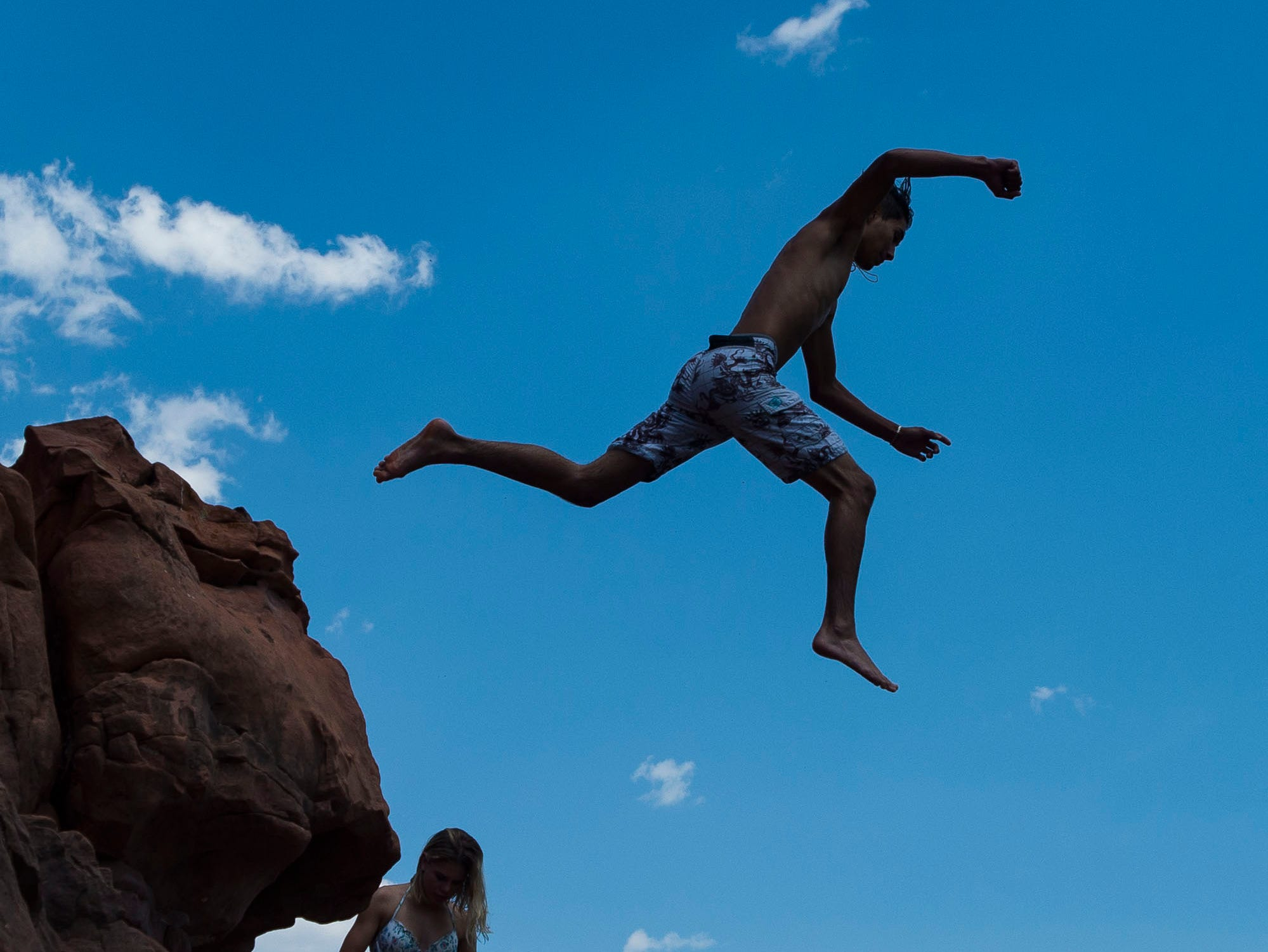 Emilio Salazar, 17, jumps off the rocky cliffside into the water while hanging out with friends on Wednesday, July 18, 2018, at Horsetooth Reservoir in Fort Collins, Colo.