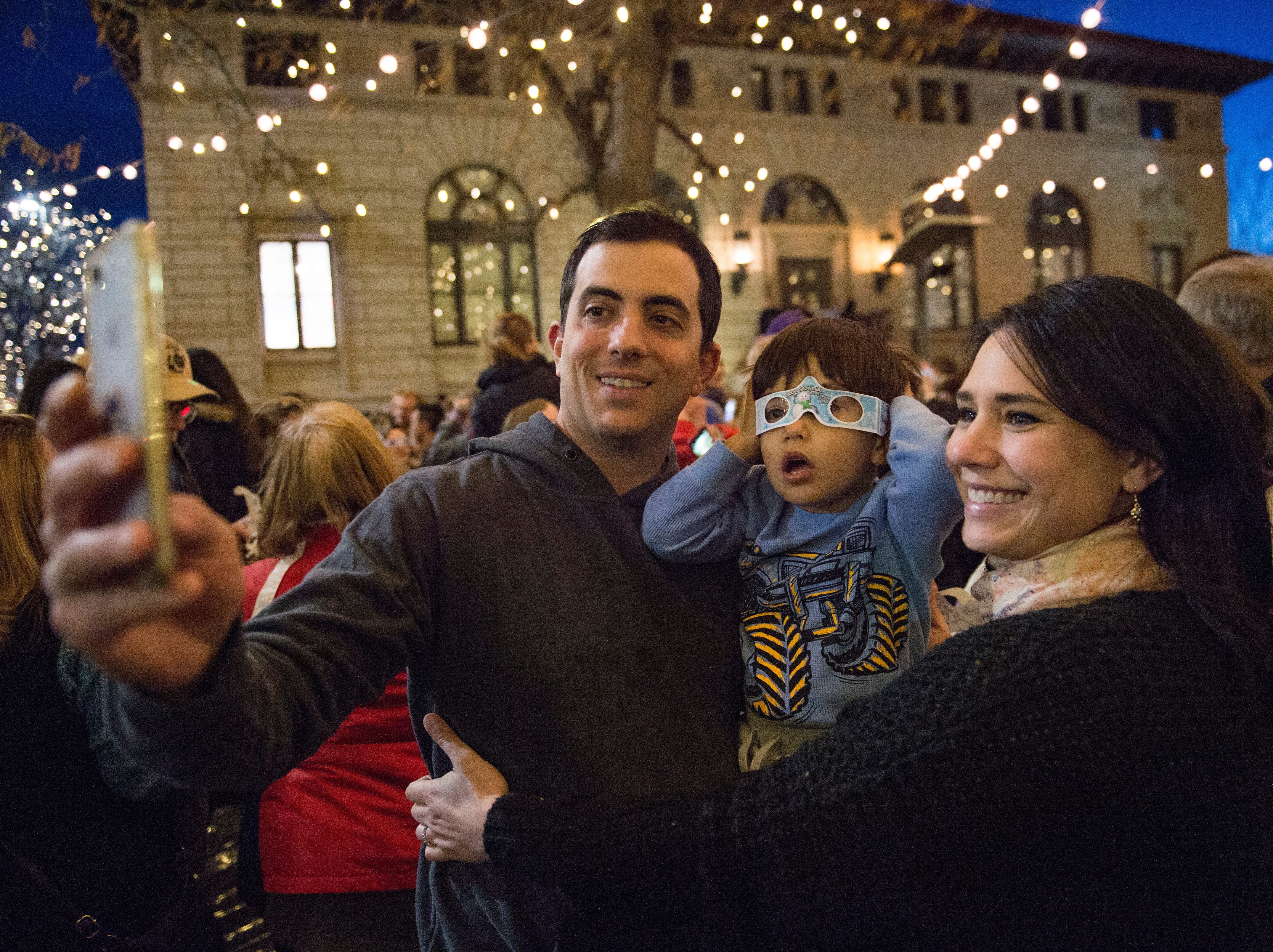 Frankie and Jennifer Basile take a photo with their son Taylor under the holiday lights in Old Town on Friday, November 2, 2018. The lights will illuminate Old Town until Feb. 14.