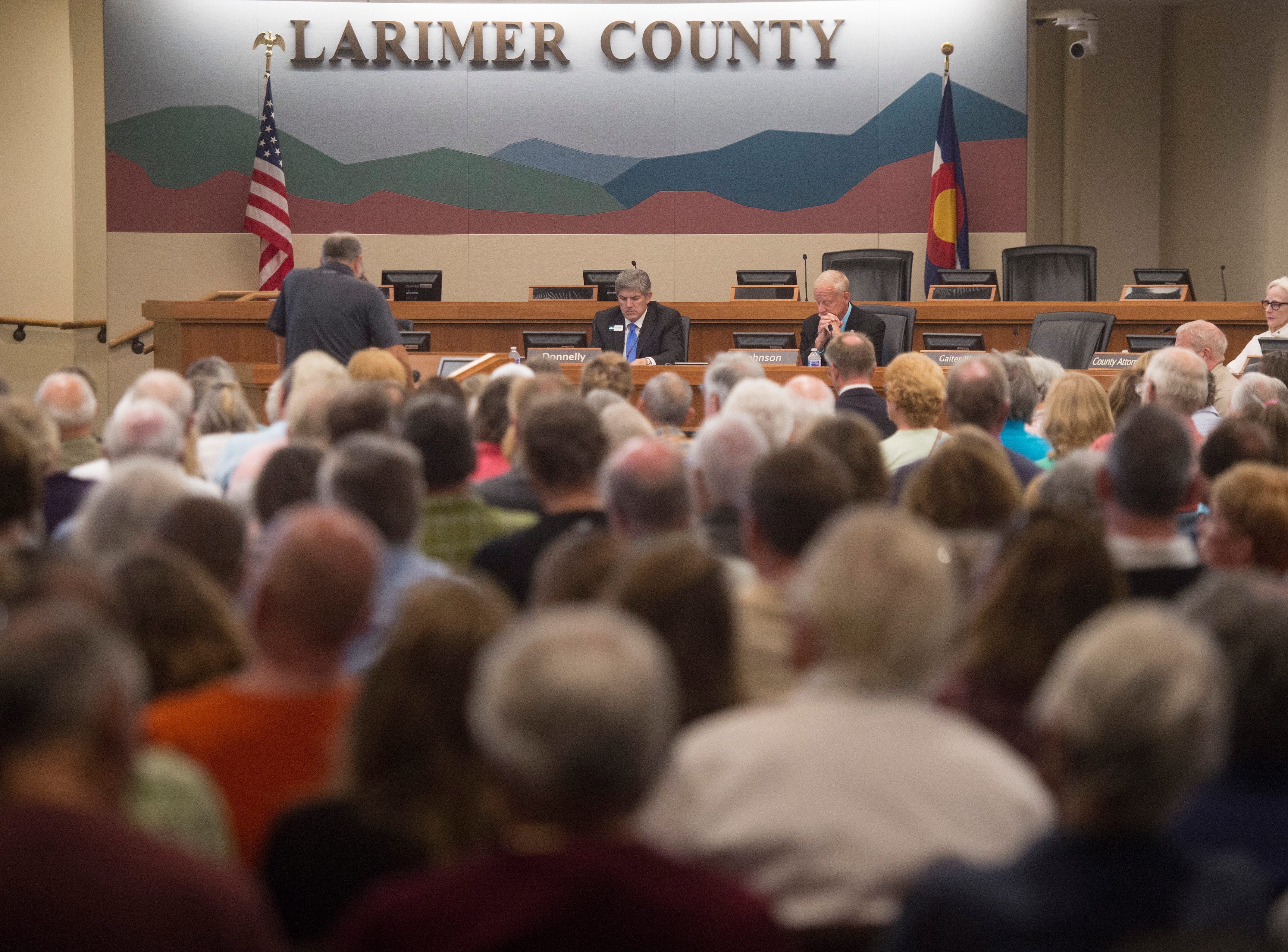 People pack a room as Larimer County Commissioners hear public comment during a hearing to permit or deny a proposed water pipeline for the City of Thornton on Tuesday, July 23, 2018.