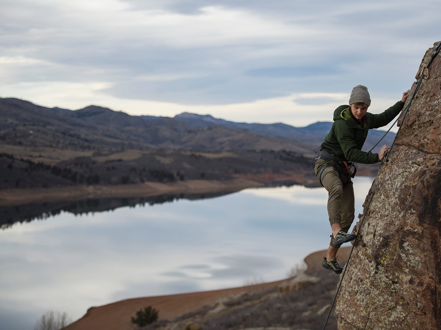 Alex Van Tress reaches the top of ledge while climbing with friends on Monday, Jan. 8, 2018, at Horsetooth Reservoir in Fort Collins, Colo.