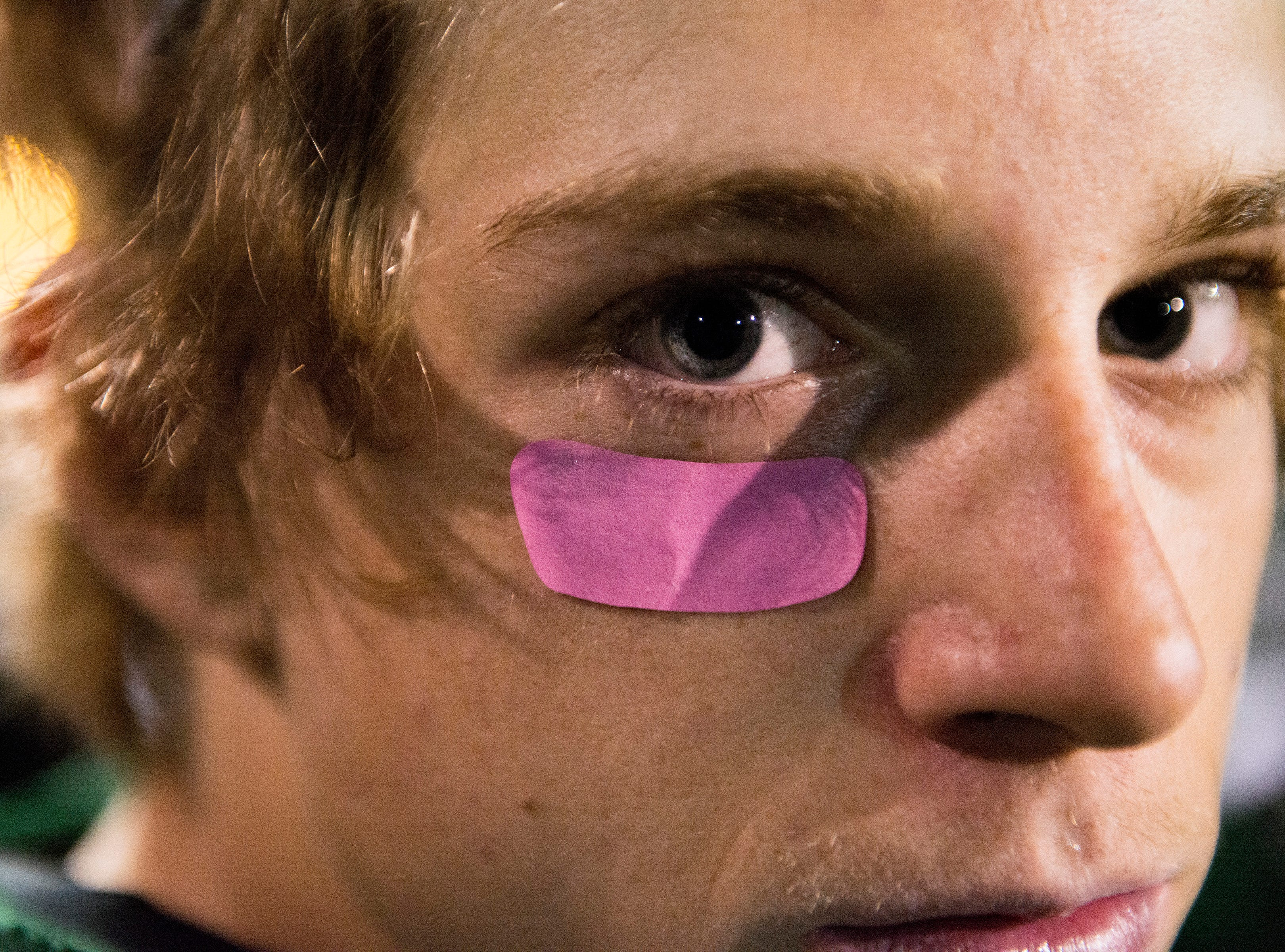 Fossil Ridge High School defensive back Ryan Ressler wears a pink anti-glare sticker below his eye to promote breast cancer awareness during a game against Rocky Mountain at French Field on Friday, October 5, 2018.