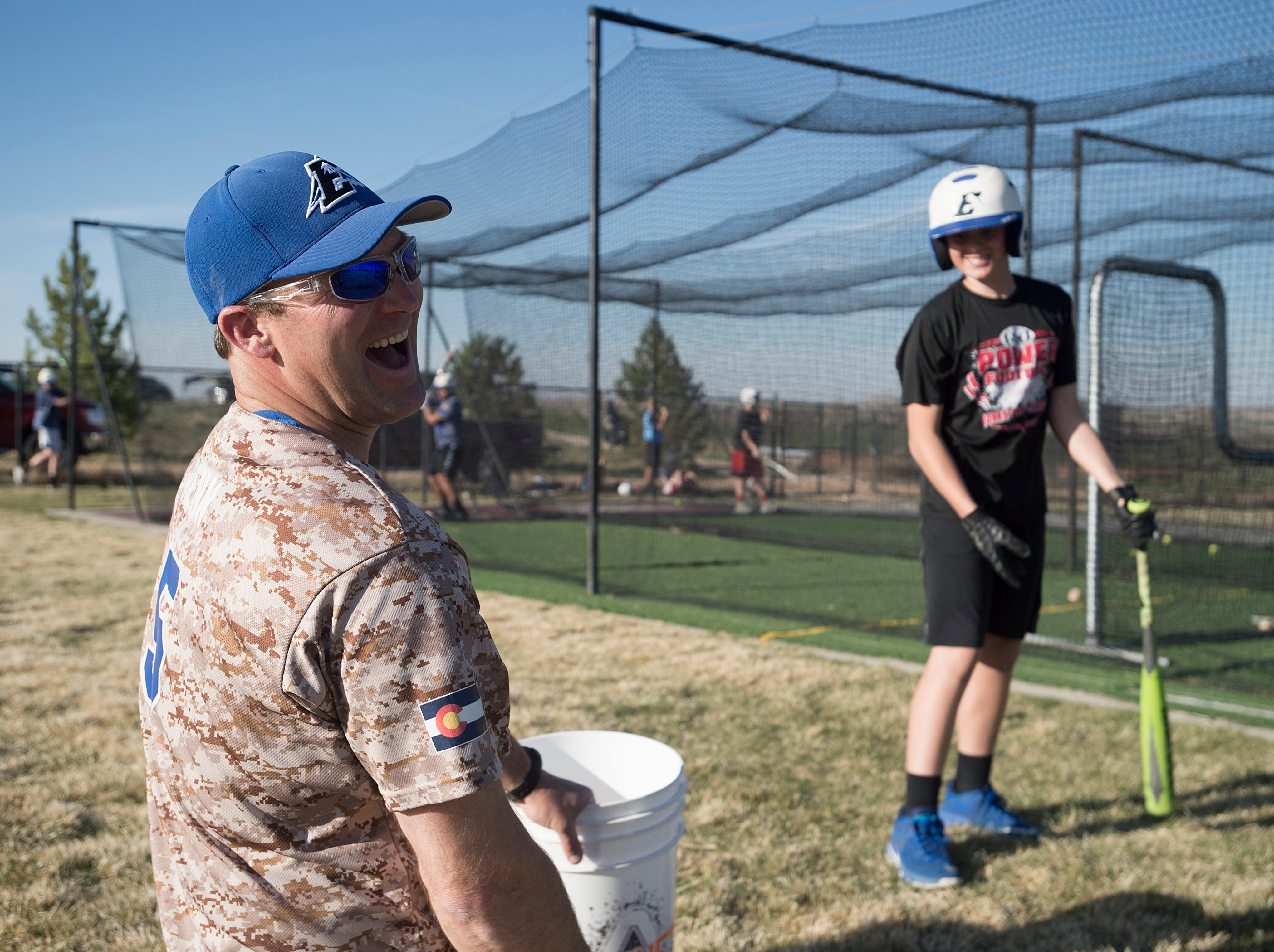 Chris Renn has a laugh with one of his players during batting practice at Nelson Farm Ball Park in Johnstown on Wednesday, April 25, 2018. Renn is head coach of the youth club team.