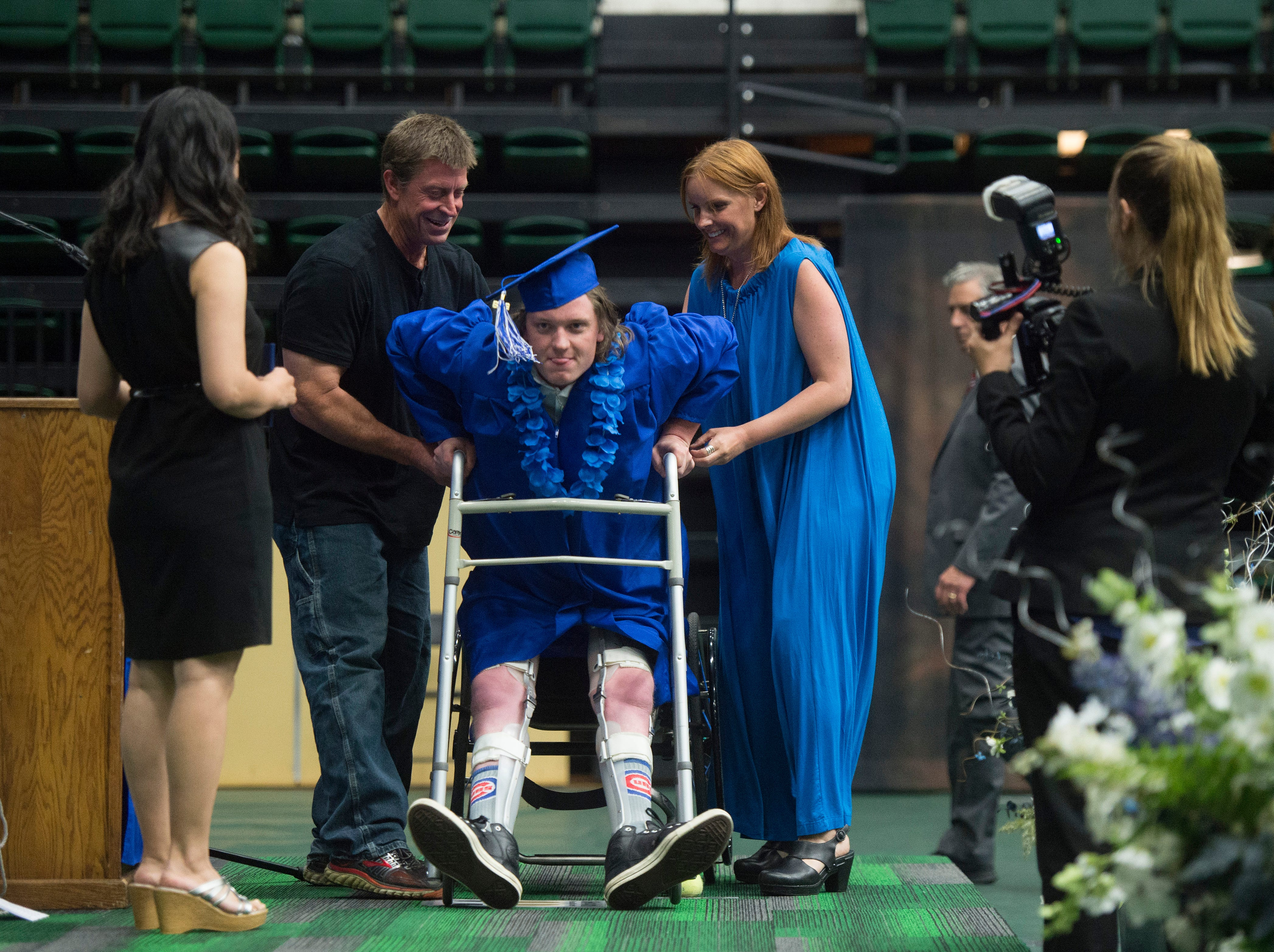 Poudre High School graduate Connor Walsh uses a walker to help him stand to receive his high school diploma during commencement at Moby Arena on Saturday, May 26, 2018. Walsh was paralyzed after being hit by a vehicle while he was walking to class in 2015.
