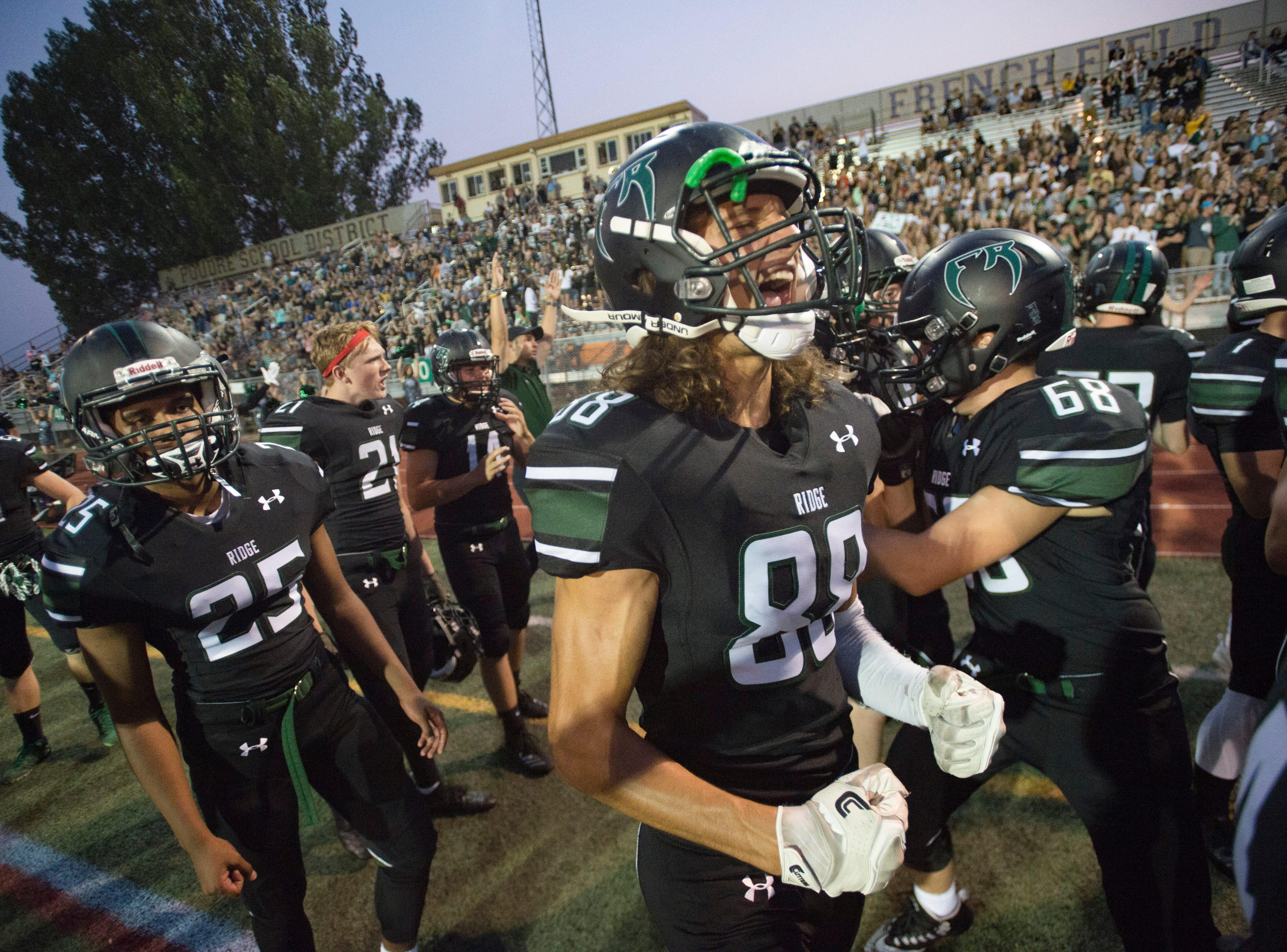 Josh Pales and the Fossil Ridge High School football team celebrate after a play in a game against Castle View at French Field on Thursday, August 23, 2018.