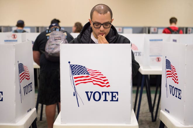 Matthew Moreno looks over his choices in the voting booth during early voting at CSU's Lory Student Center on Monday, November 5, 2018. Election judges said a steady stream of students were turning out to vote the day before Election Day.