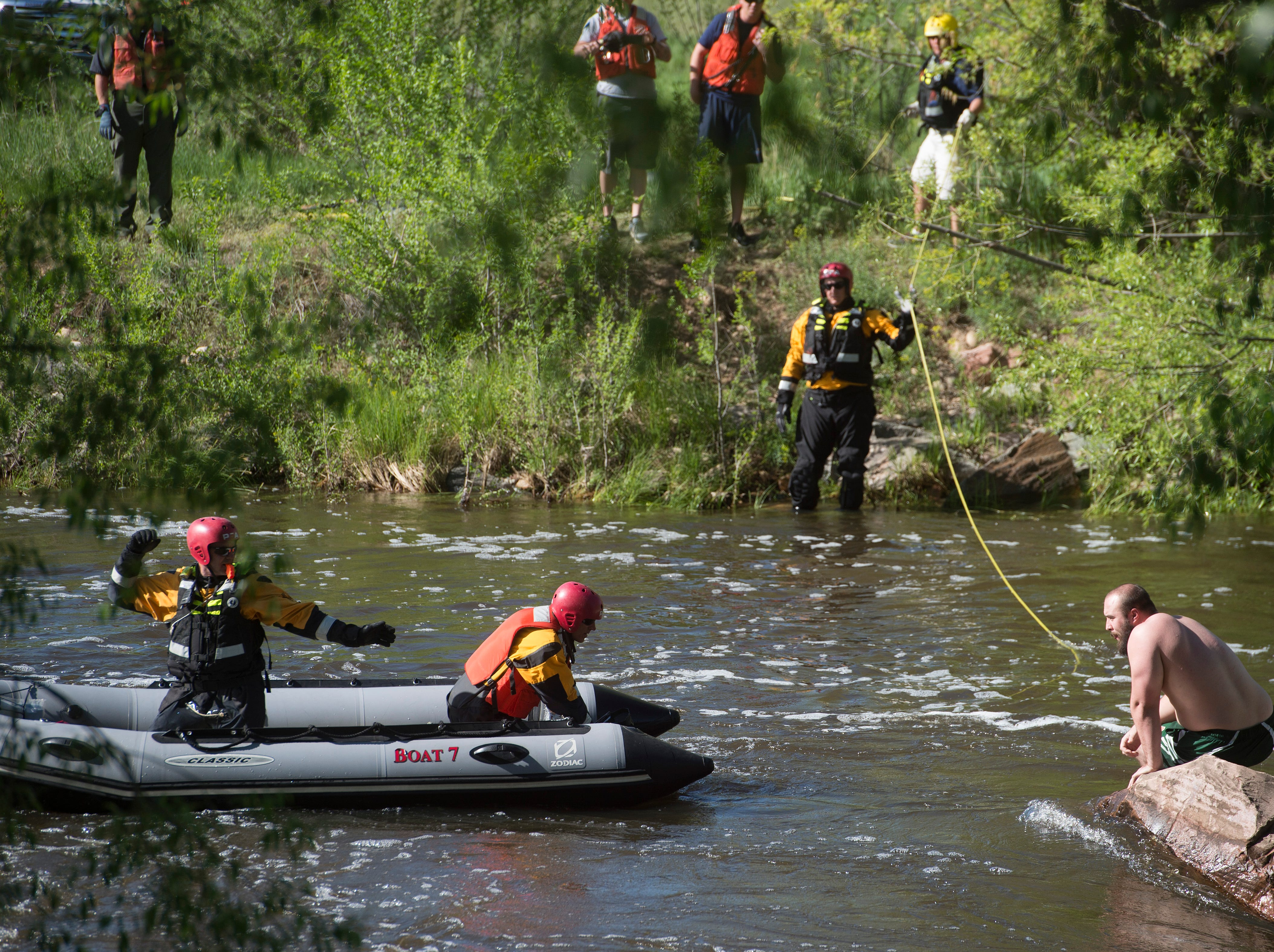 Rescuers inch closer to a man stranded in the middle of fast current on the Poudre River near College Avenue on Wednesday, May 16, 2018.