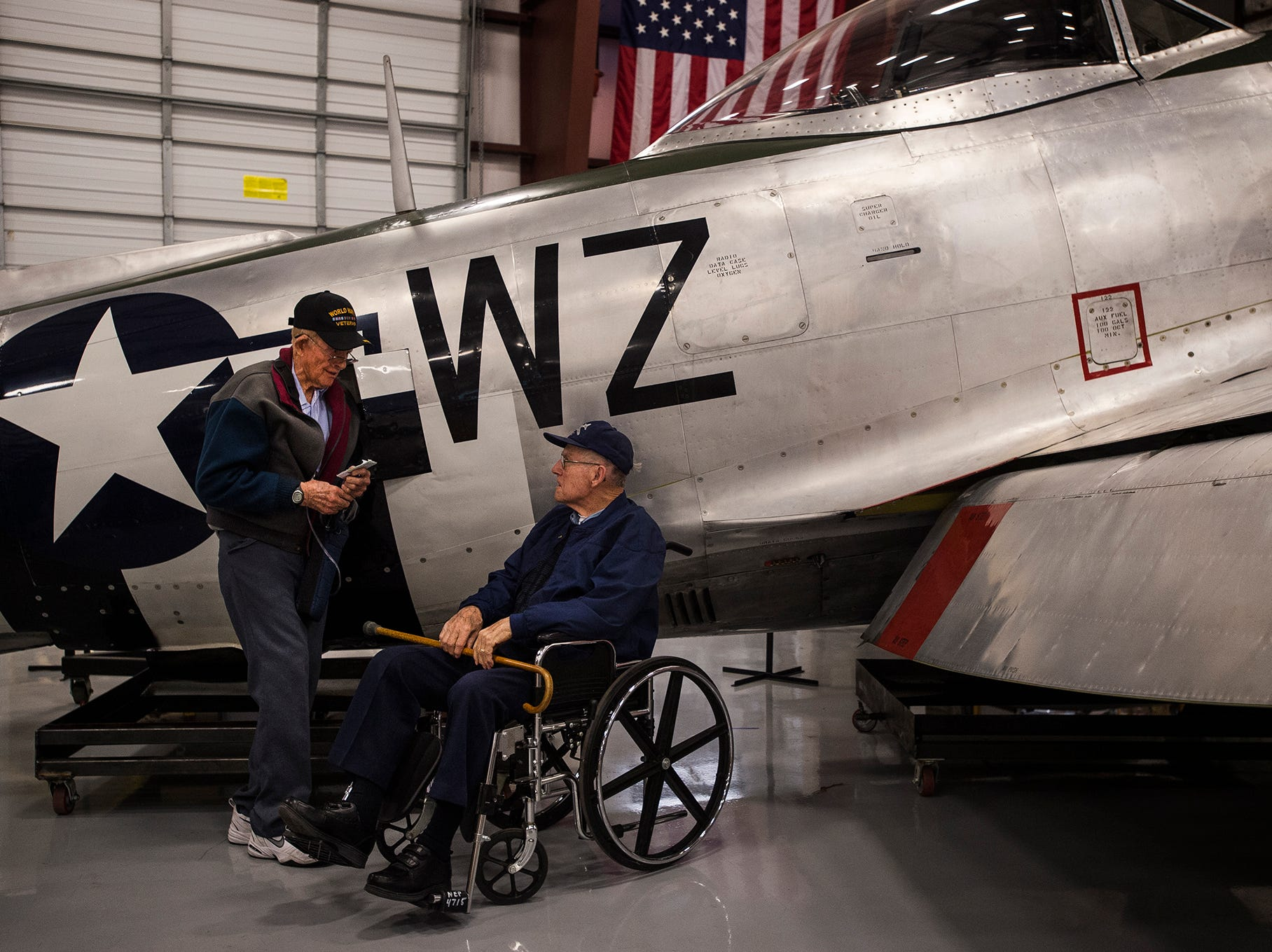 World War II Army Air Corp veterans Philip Daily, left, and Lee Bashor talk next to a Republic P47D-40 Thunderbolt fighter plane on Saturday, May 5, 2018, at the National Museum of World War II Aviation in Colorado Springs, Colo.