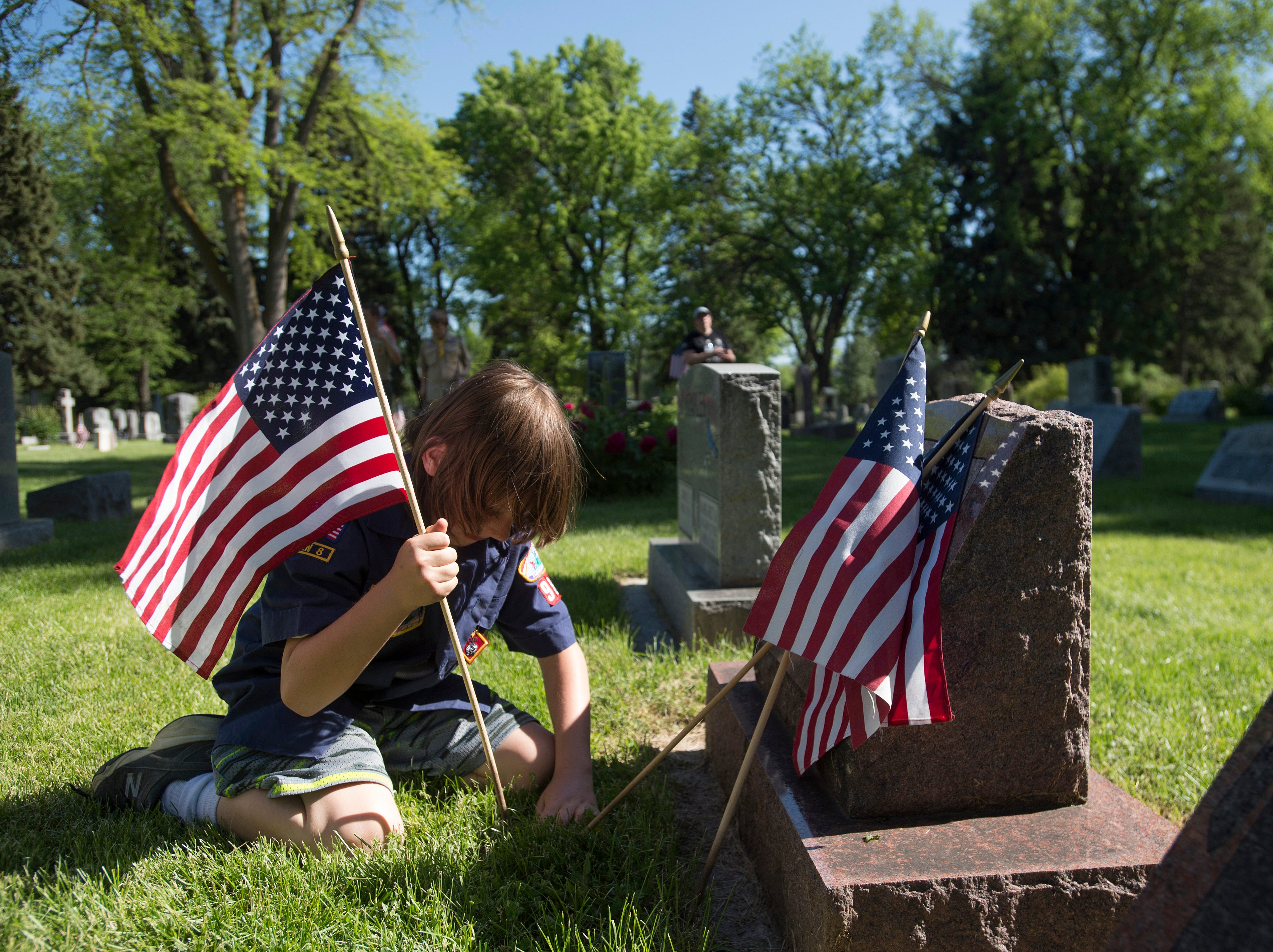 Matthew Young of Fort Collins' Pack 98 drives a United States Flag into the ground in front of a veteran's headstone at Grandview Cemetery at on Wednesday, May 23, 2018. Cub Scouts and Boy Scouts have been placing thousands of flags to honor veterans in the cemetery for around 40 years.