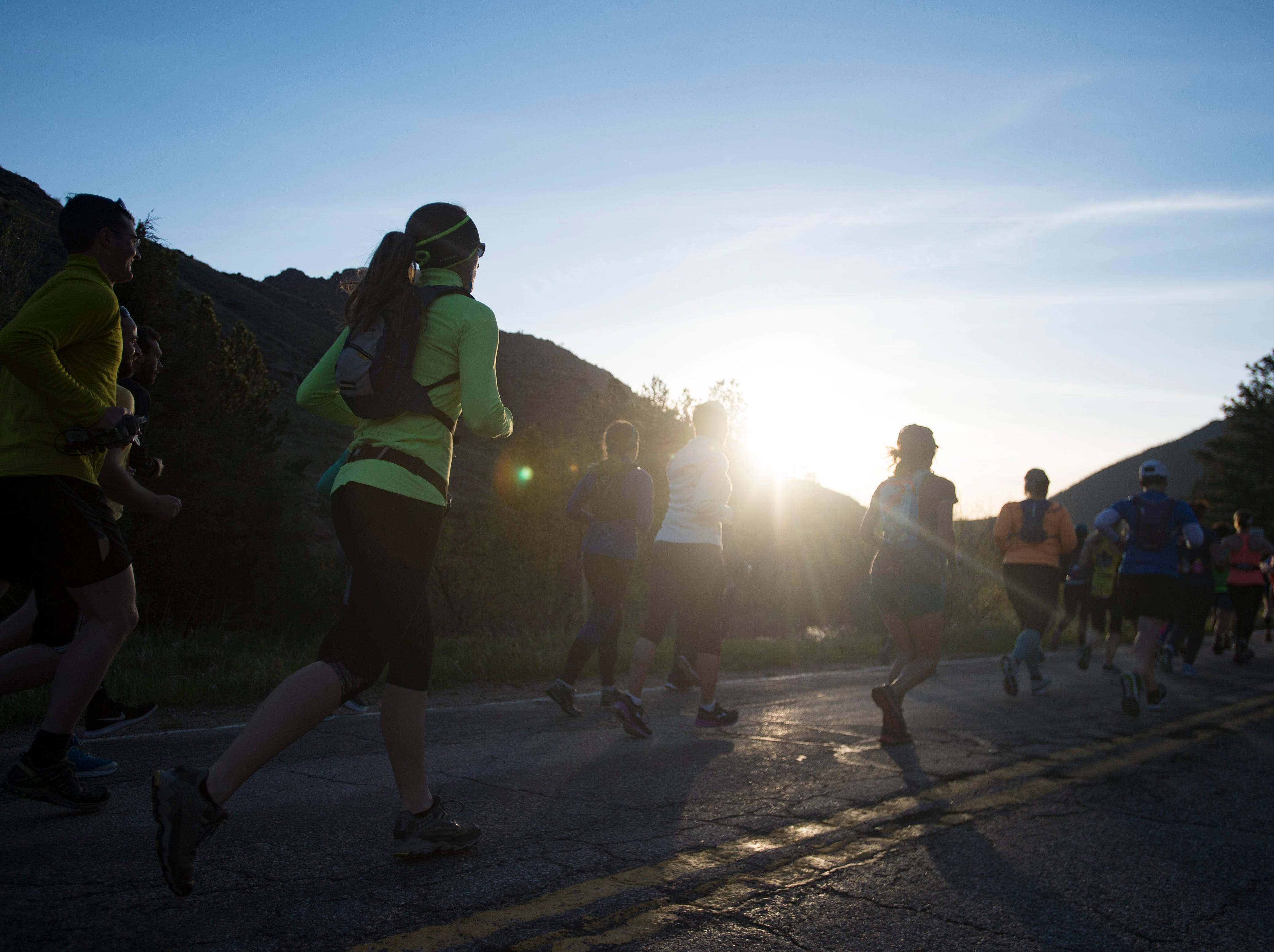 The sun rises over the foothills as runners move through Poudre Canyon during the Colorado Marathon on Sunday, May 6, 2018.