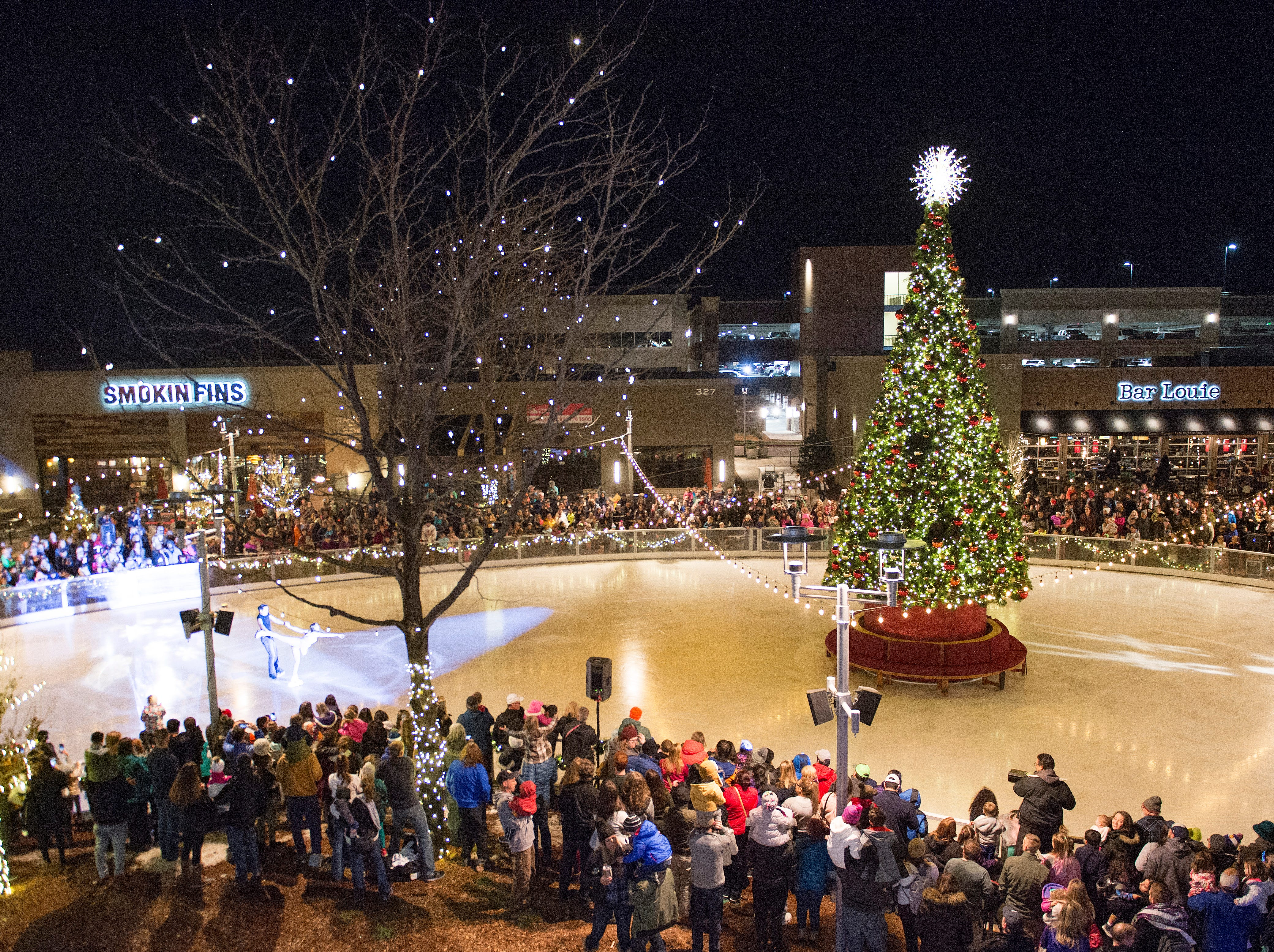A crowd attends a tree lighting and ice skating performance at Foothills Mall on Friday, November 16, 2018.