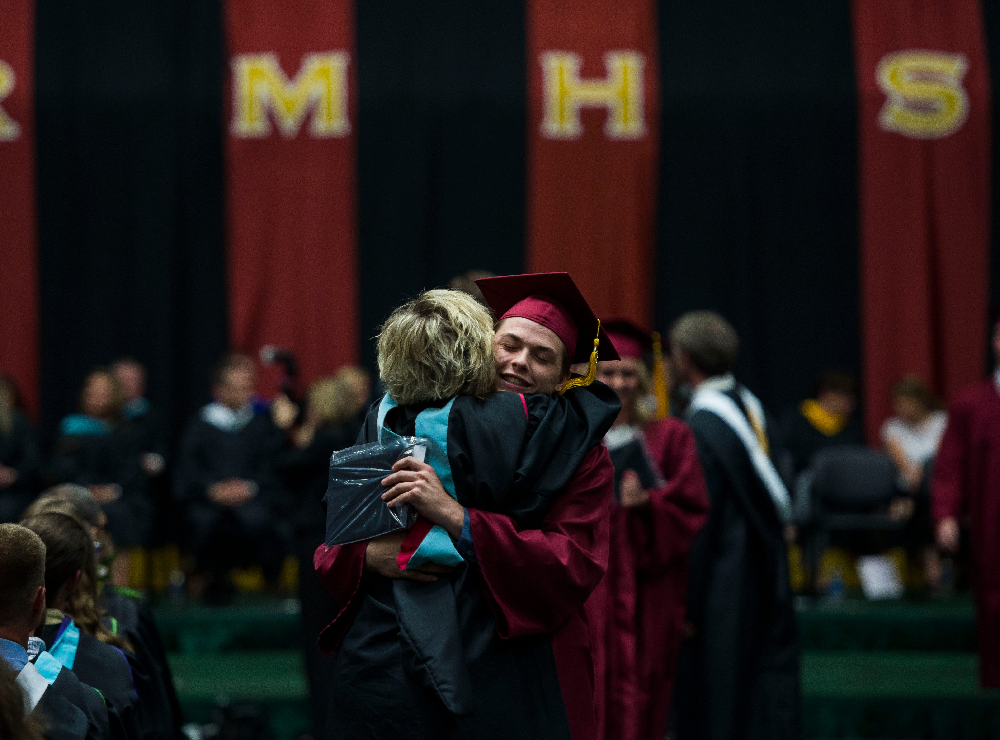 Rocky Mountain High School senior Conner Austin-Jones hugs teacher Ms. Laura Druse after receiving his diploma at his graduation ceremony on Friday, May 25, 2018, at Moby Arena in Fort Collins, Colo.