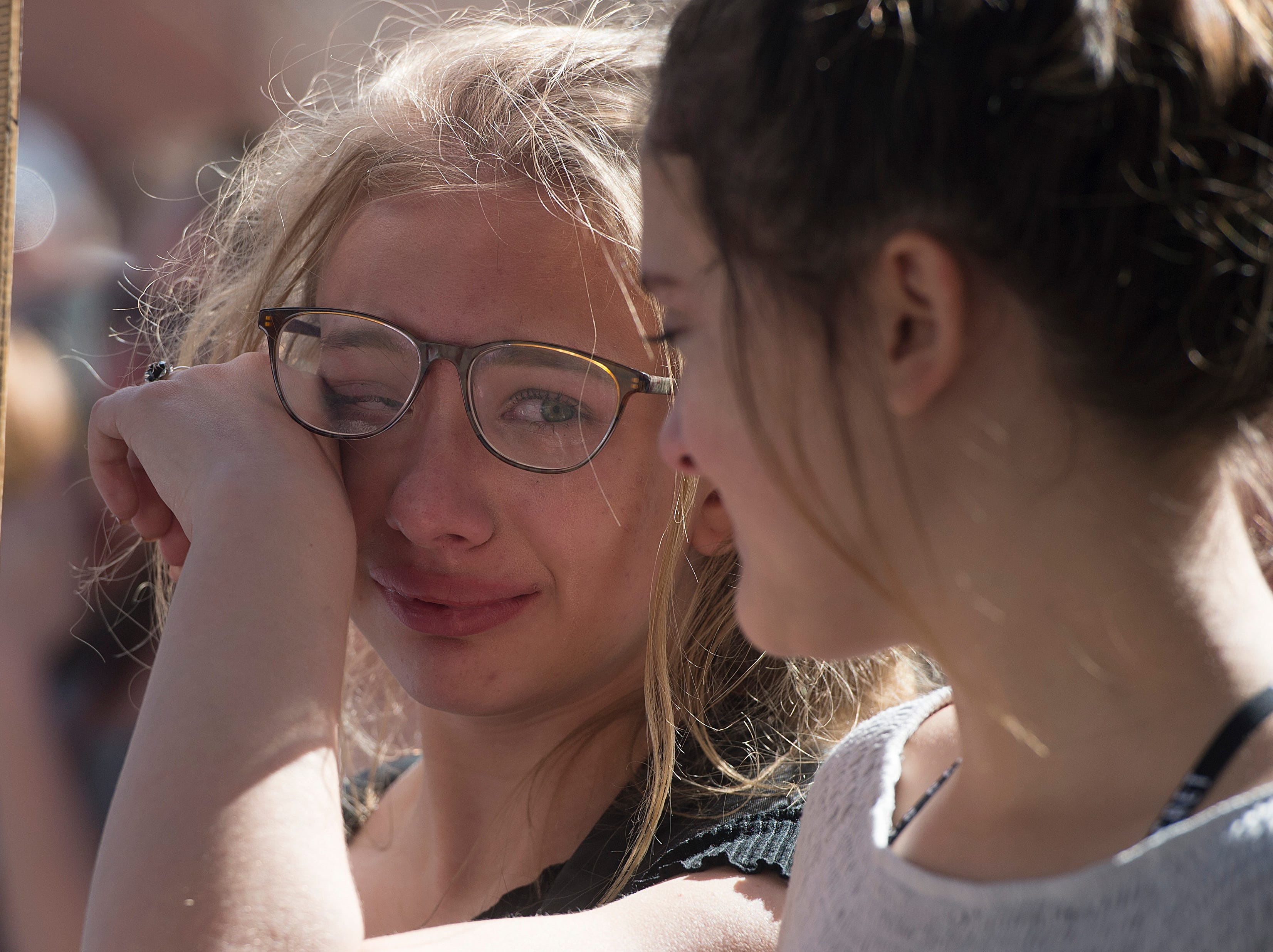 Bella Swanson, 13, wipes a tear away as she looks to her friend Bonnie Torres during a March for Our Lives event on Saturday, March 24, 2018. The gathering was a part of the national movement following the Parkland, Florida shooting last month.