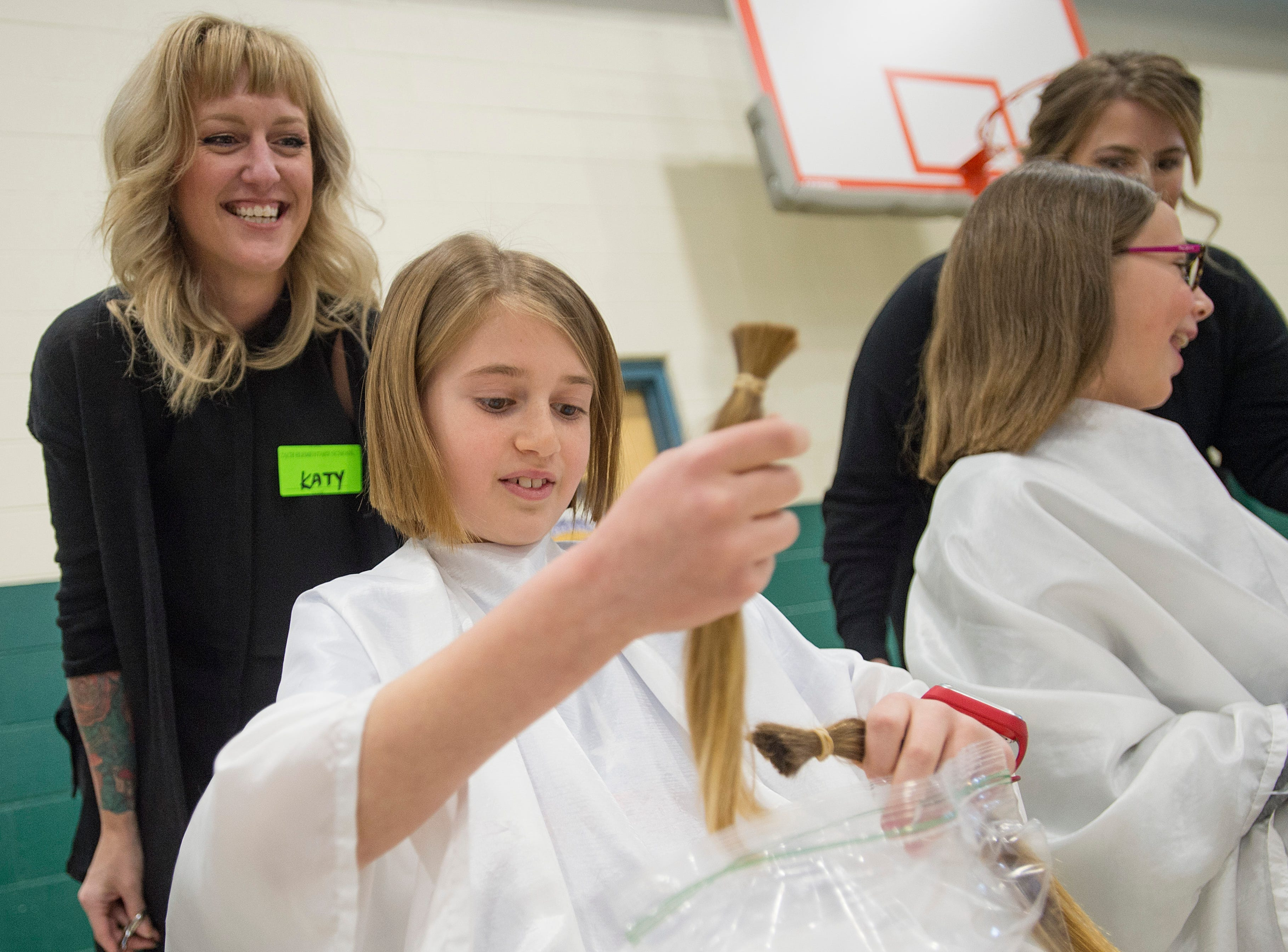 Jason Mynatt secures bundles of his hair in a bag after a hair donation assembly at Zach Elementary School on Friday, January 26, 2018. Mynatt, a fourth grader, grew his hair out for three years just so he could donate to Locks of Love.