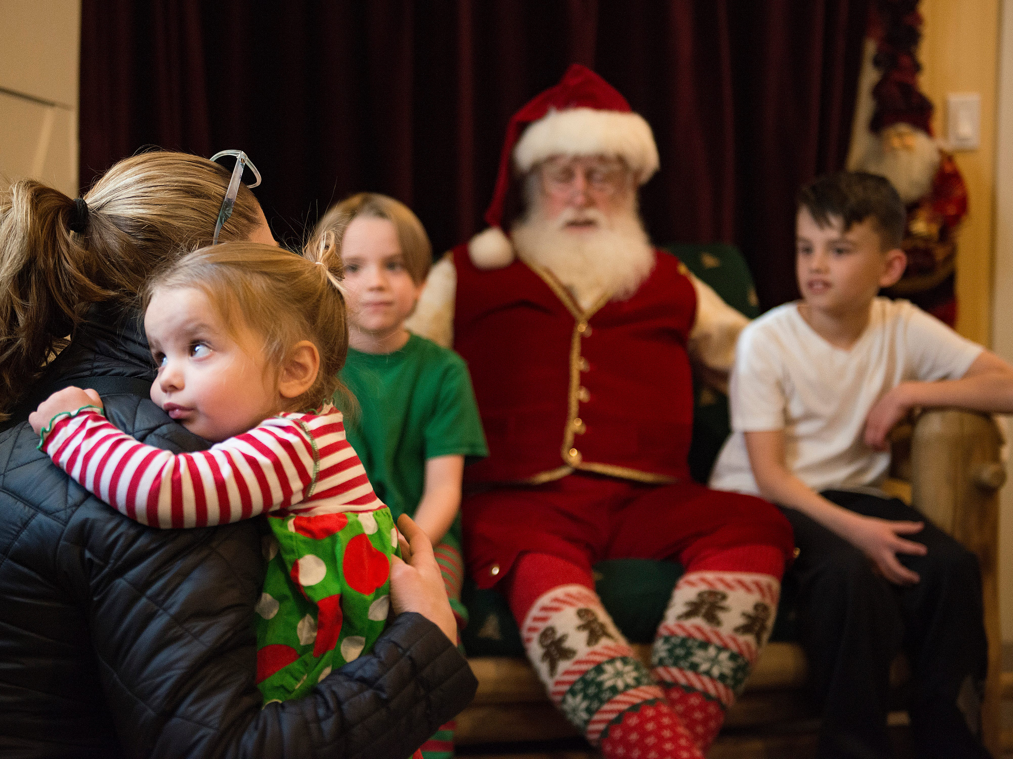 Caroline Housley, 2, holds onto her mother, Kristi, as she visits Rick Price portraying Santa Claus with her brothers Graham and Grady in Old Town Square on Thursday, December 13, 2018.