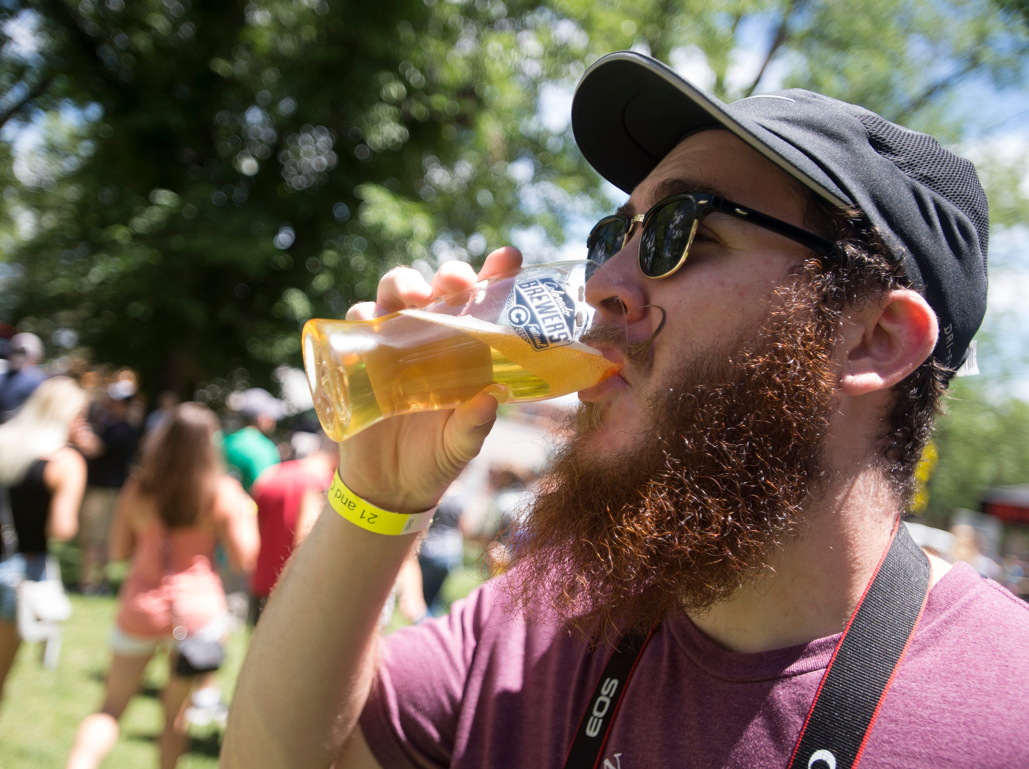 Dylan Hochstedler sips a beer at the Colorado Brewers' Festival in Washington Park on Friday, June 22, 2018. The festival returned for its 29th year with over 100 craft brews from around the state.