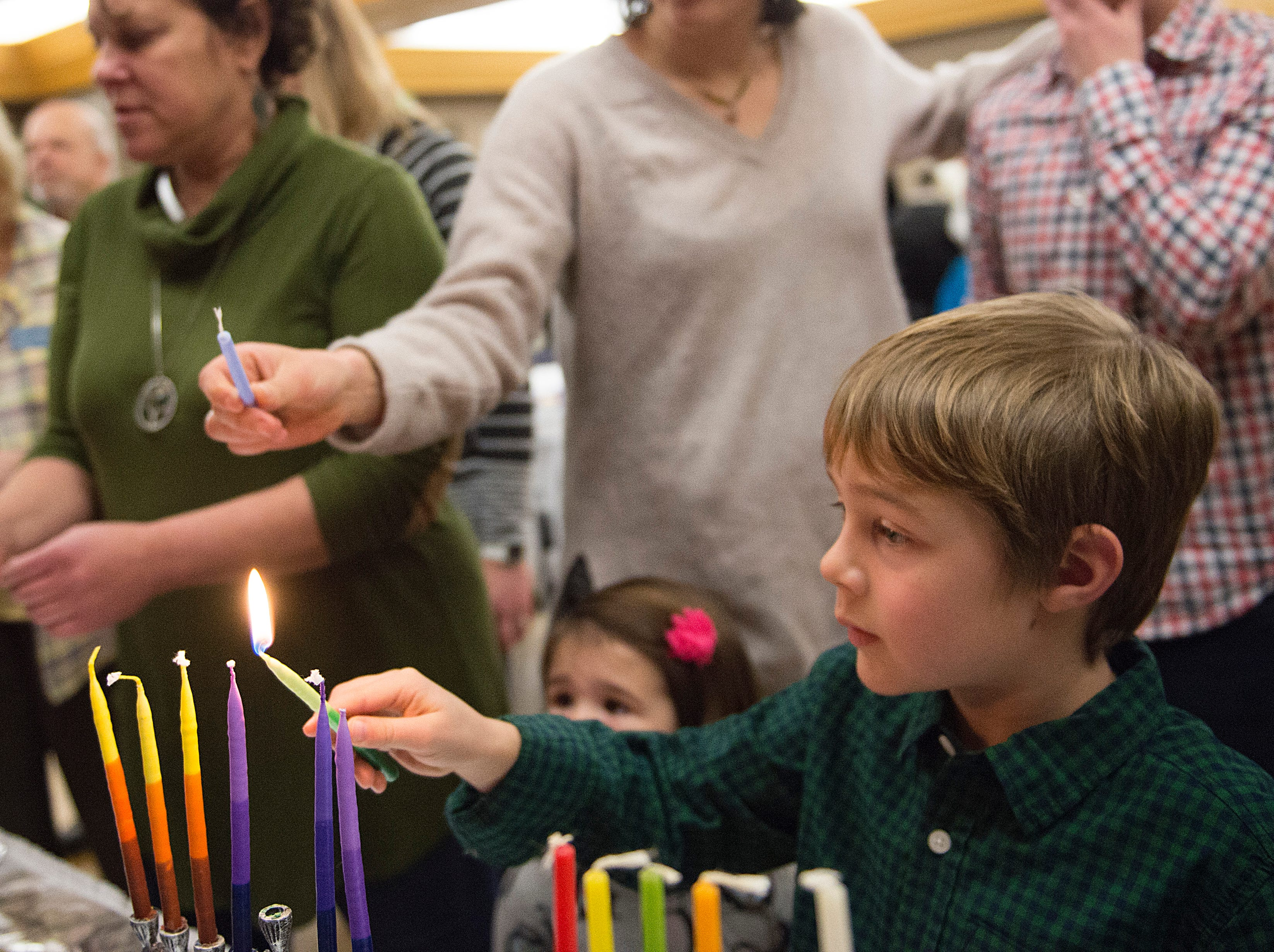 Odin Christiansen lights candles on the menorah on the sixth night of Hanukkah during a family gathering with Temple Or Hadash at the Fort Collins Senior Center on Friday, December 7, 2018.