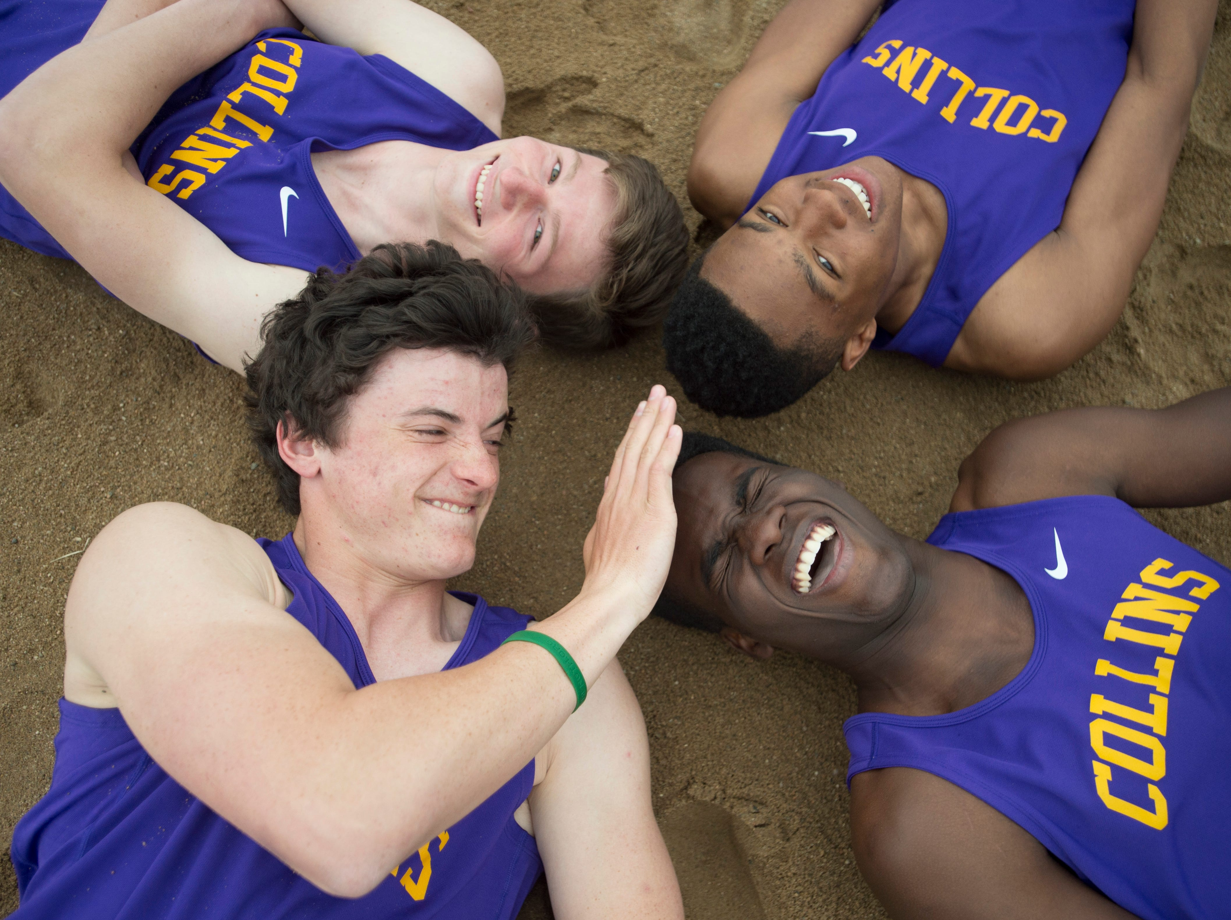 Fort Collins High School long jumpers Allam Bushara, Micaylon Moore, Joey Maguire and Spencer Purnell goof off in the sand pits during practice on Tuesday, April 24, 2018.