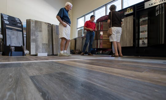 Peter D'elia and Peggy Rinaldi, of Estero, look at flooring options with the assistance of sales associate James Kelly, during their visit to Direct Flooring in Cape Coral.