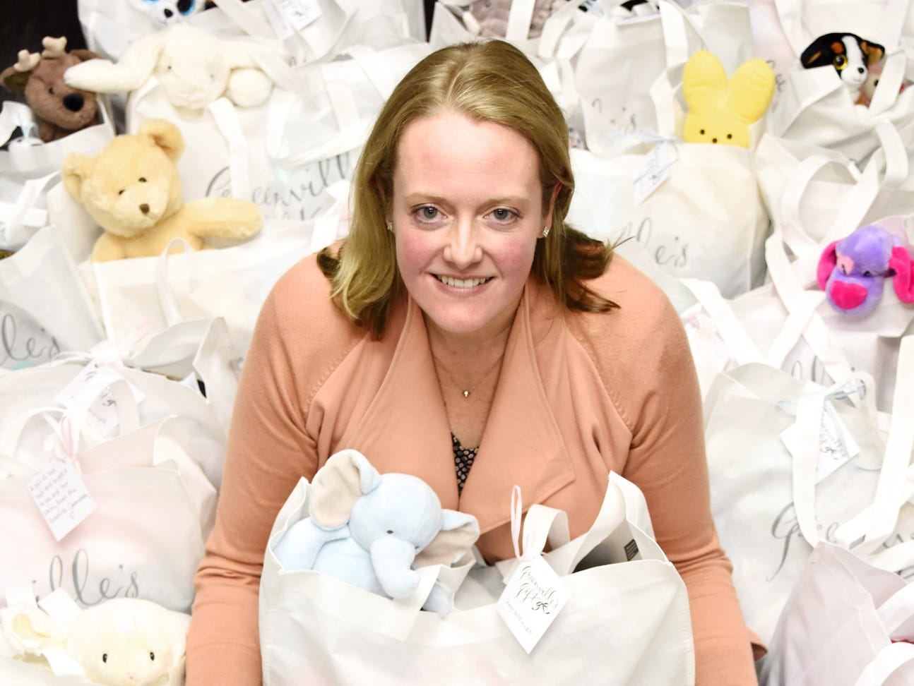 Marshall Johnson, founder of Greenville's Gift, sits with many of the bags that the organization gives to mothers in need.