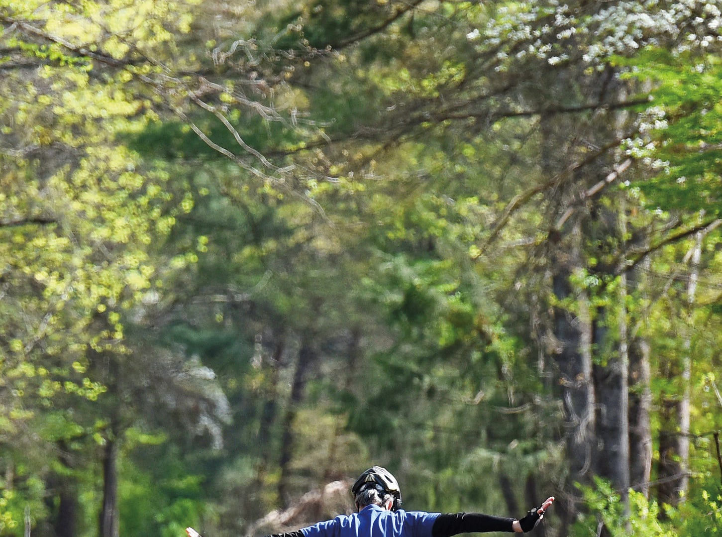 A cyclist stretches his arms out while riding down the Swamp Rabbit Trail near Furman University.