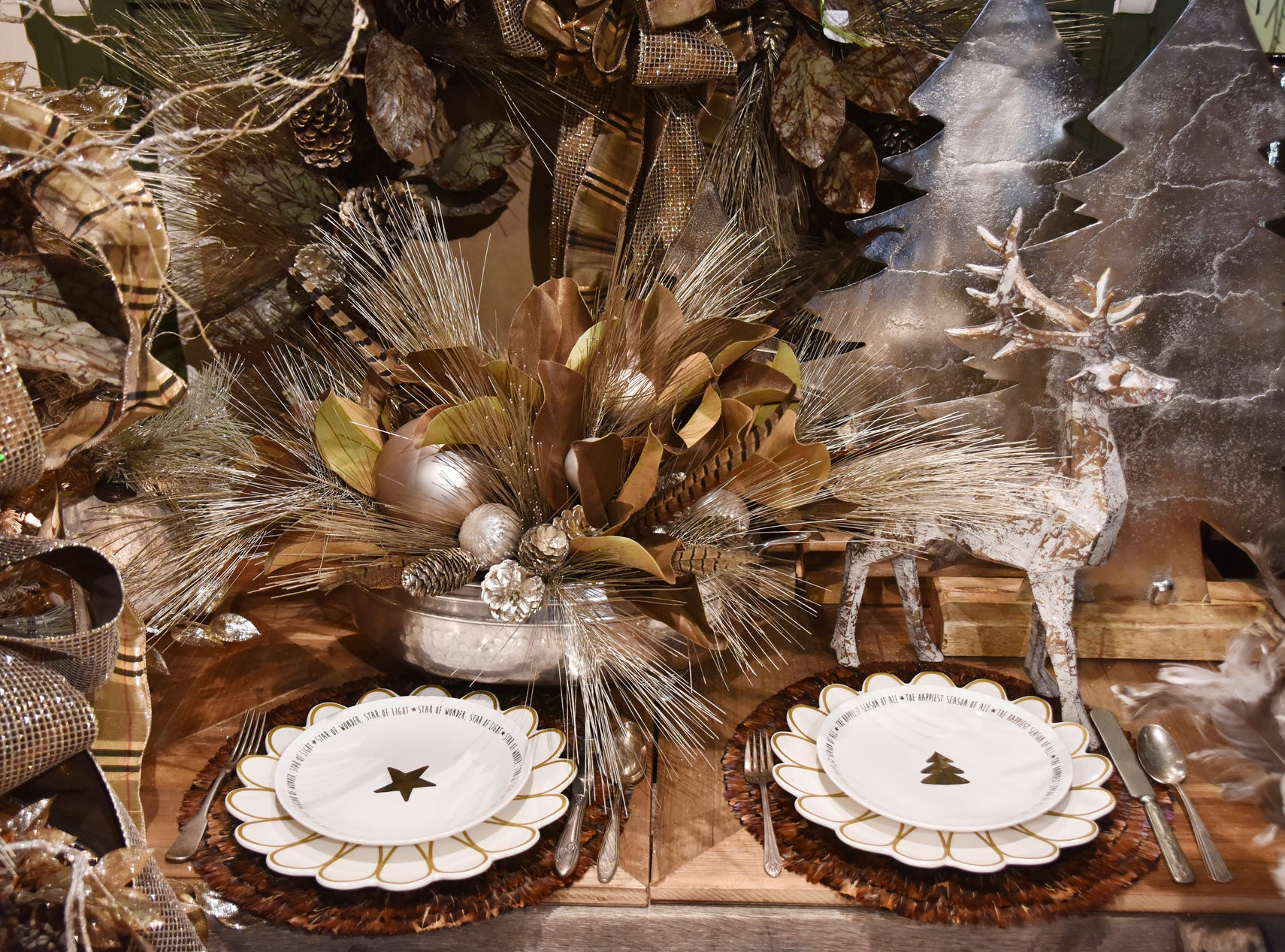 A tablescape with mixed plantinum, browns, bronzes tones and feathers for a sophisticated woodsy look.