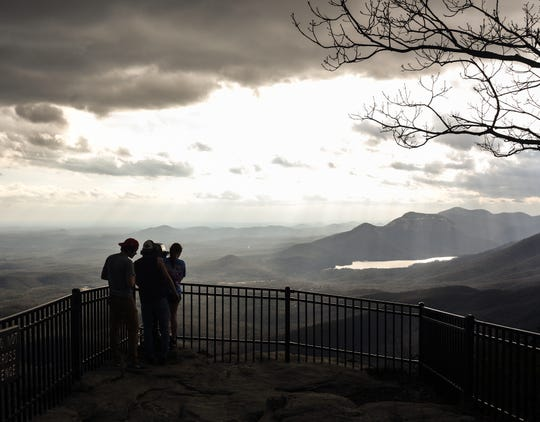 People take in the view of Table Rock from an observation deck at Caesers Head State Park.