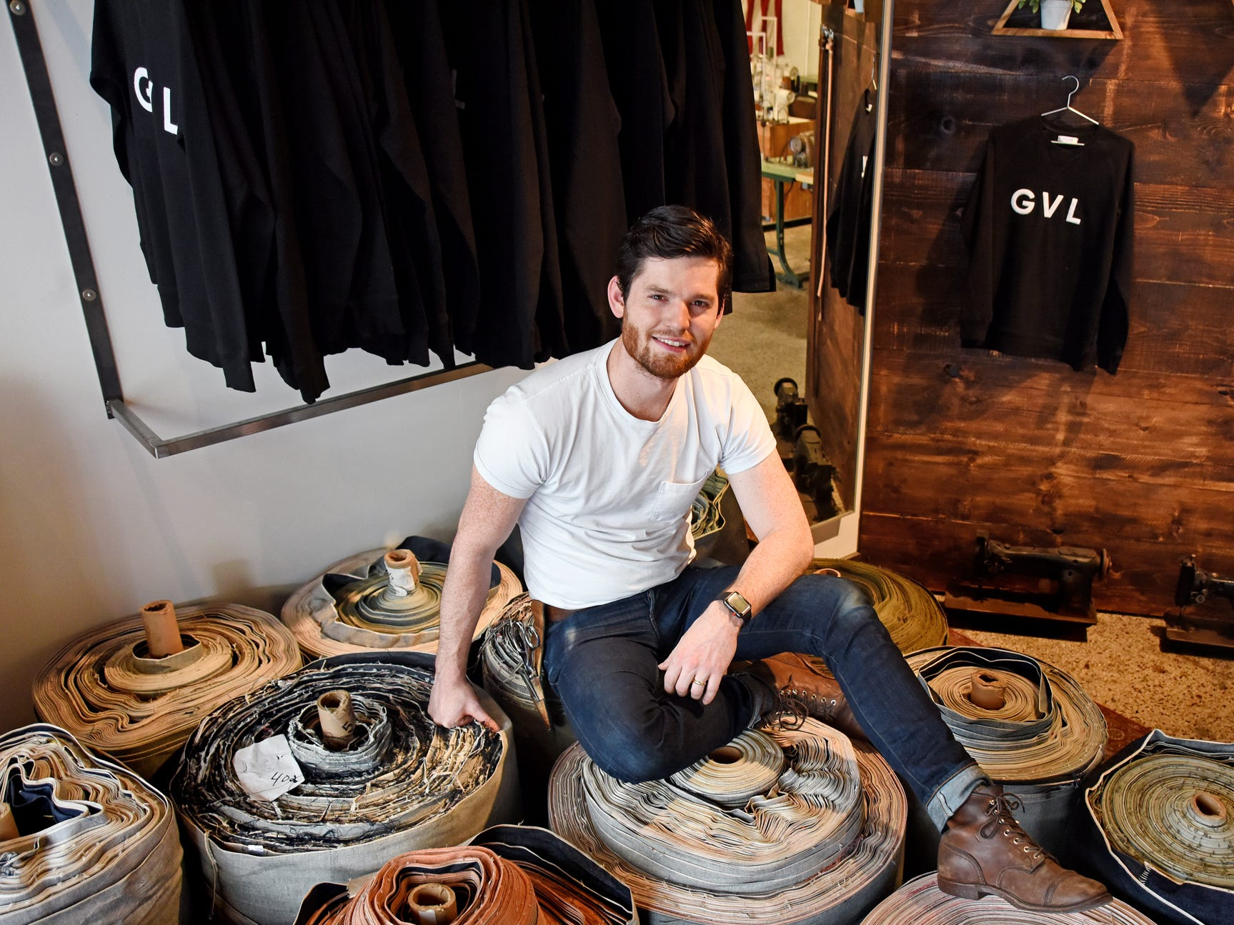 Bill Mitchell, owner of Billiam Jeans in Greenville, sits on rolls of denim in his store.