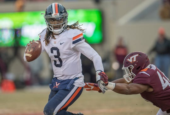 Virginia quarterback Bryce Perkins (3) avoids a Virginia Tech Hokies tackler at Lane Stadium. Perkins has thrown for 2,472 yards and rushed for 842 this season.