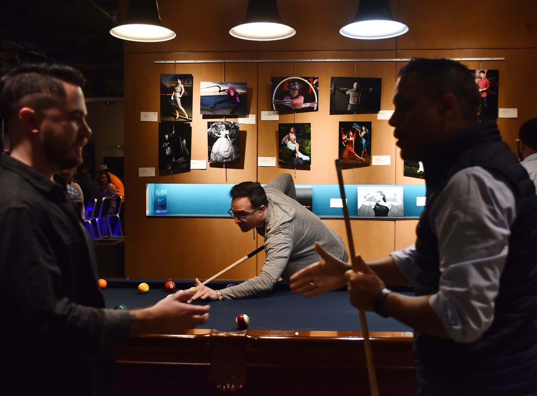 People play a game of pool in the WXYZ Lounge at Aloft in downtown Greenville.
