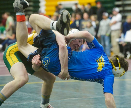 CMR's Carter Carroll lifts Great Falls Central's Lars Madson during the CMR Holiday Classic Wrestling Tournament in the Russell Fieldhouse last December.